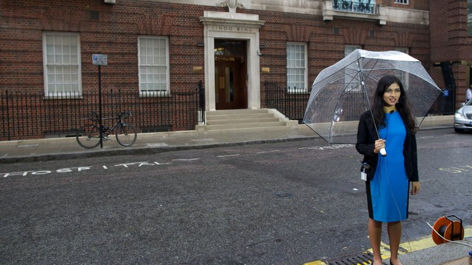 A reporter prepares to go on camera outside the Lindo Wing at St Mary's Hospital in London on June 20, 2013. Prince William's wife Catherine is not officially due to give birth for two weeks but the world's media began gathering outside the London hospital where she will have the baby, determined not to miss the photograph of the year.