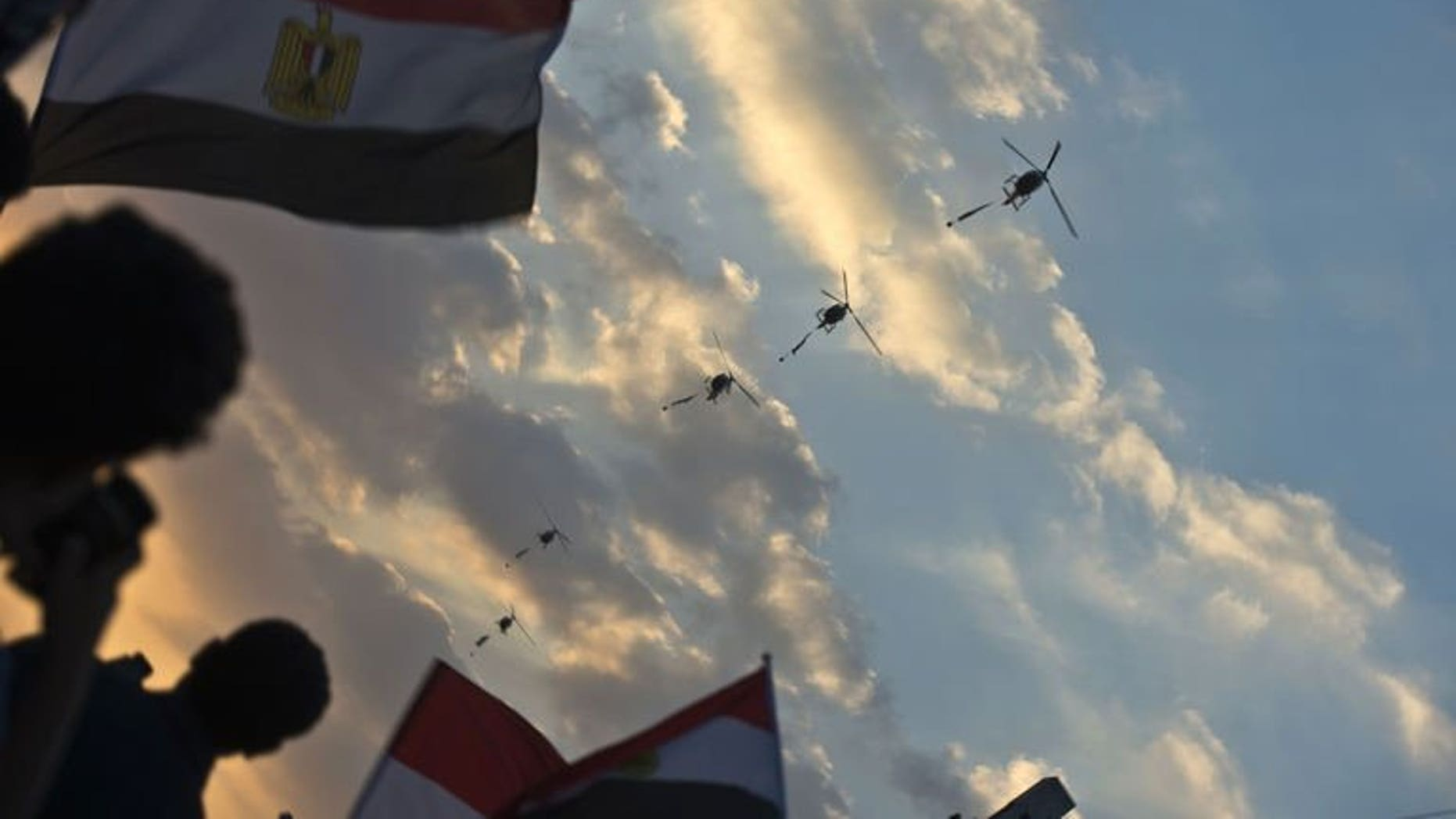 Egyptian army helicopters fly over as hundreds of thousands of Egyptian demonstrators gather outside the presidential palace in Cairo during a protest calling for the ouster of President Mohamed Morsi on July 1, 2013.