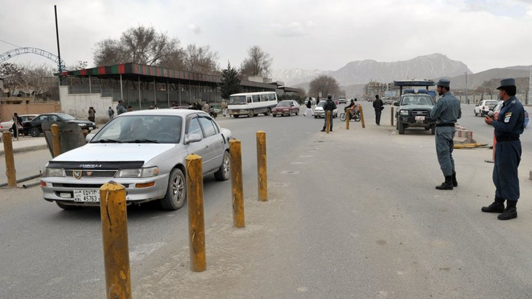 In this file photo, Afghan policemen are seen standing guard at a checkpoint in Kabul, on March 23, 2012. A suicide car bomb in Kabul struck a foreign logistics company supplying NATO forces, killing one person and wounding three or four others early on Tuesday, police said.