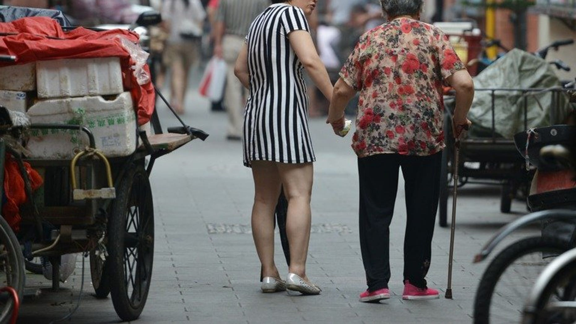 """A mother and daughter are seen walking together in Shanghai, on July 1, 2013. The Law on Protection of the Rights and Interests of the Elderly says family members should visit relatives who are aged over 60 """"often"""" -- but does not give a precise definition of the term. More than 14 percent of China's population, or 194 million people, are aged over 60, according to the most recent figures."""