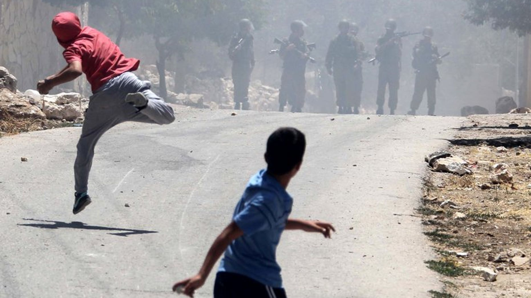 Palestinian protesters throw stones towards Israeli security forces during clashes near the West Bank city of Nablus, on June 28, 2013. A Palestinian teenager was knocked down and killed by an Israeli military jeep during overnight clashes in a village in the southern West Bank, Palestinian police and witnesses told AFP.