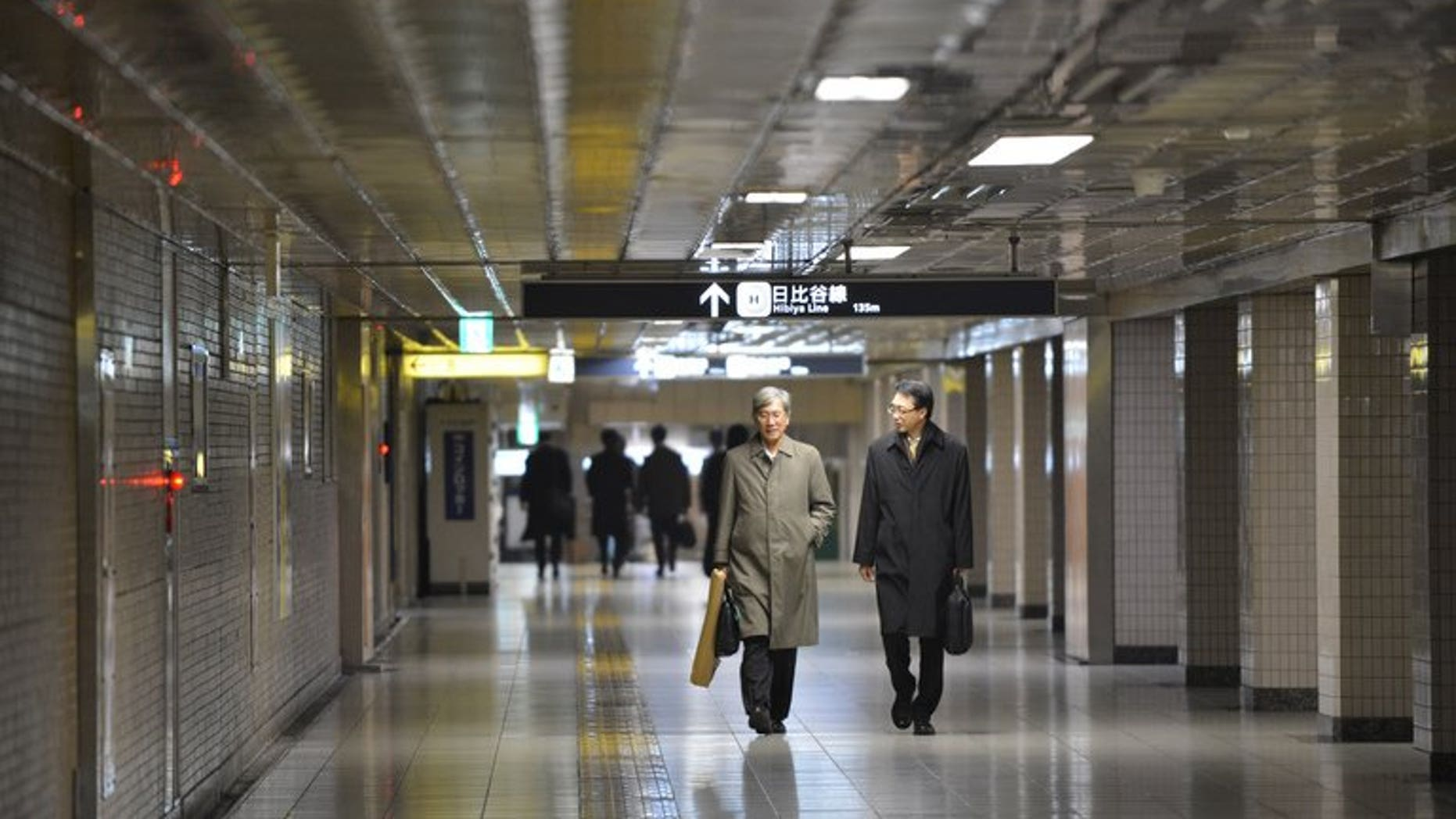 Businessmen walk on a concourse at a subway terminal in downtown Tokyo on December 28, 2012. Japan's army of dark-suited salarymen are scraping by on a monthly allowance from their wives that is less than half what they got in the 1980s bubble years, a survey has shown.