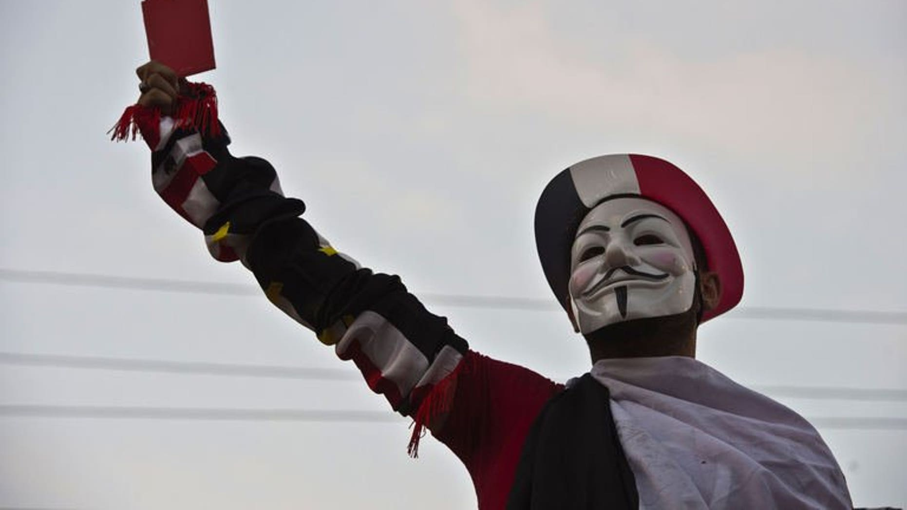A protester wearing a Guy Fawkes mask holds up a red card as thousands of Egyptian demonstrators gather outside the presidential palace in Cairo, on July 1, 2013. US President Barack Obama has called President Mohamed Morsi to warn him that the voices of all Egyptians must be heard as a political crisis escalates, the White House said.