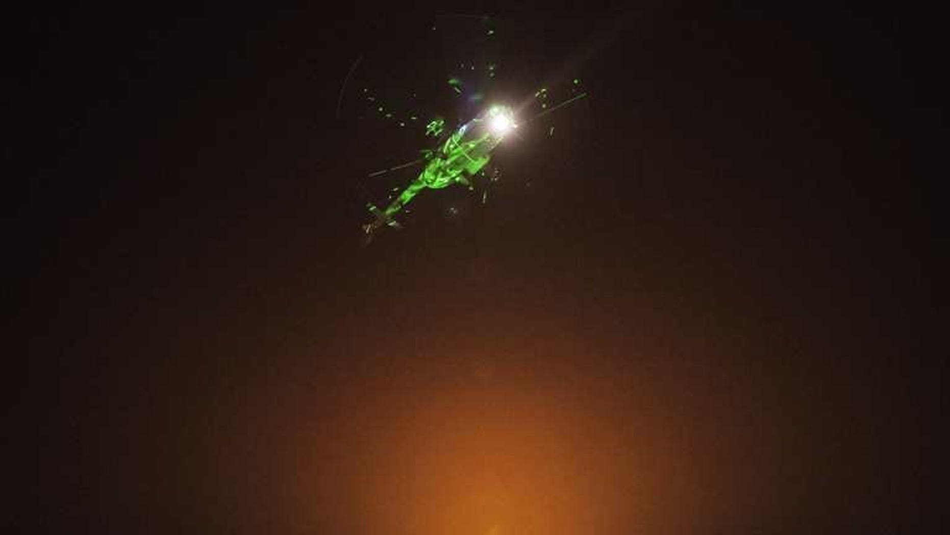 """Egyptian protesters direct laser lights on a military helicopter flying over the presidential palace in Cairo, on July 1, 2013. Iran on Tuesday called on the Egyptian military to support national reconciliation and respect the """"vote of the people"""" after it warned it was ready to intervene in Egypt's political crisis."""