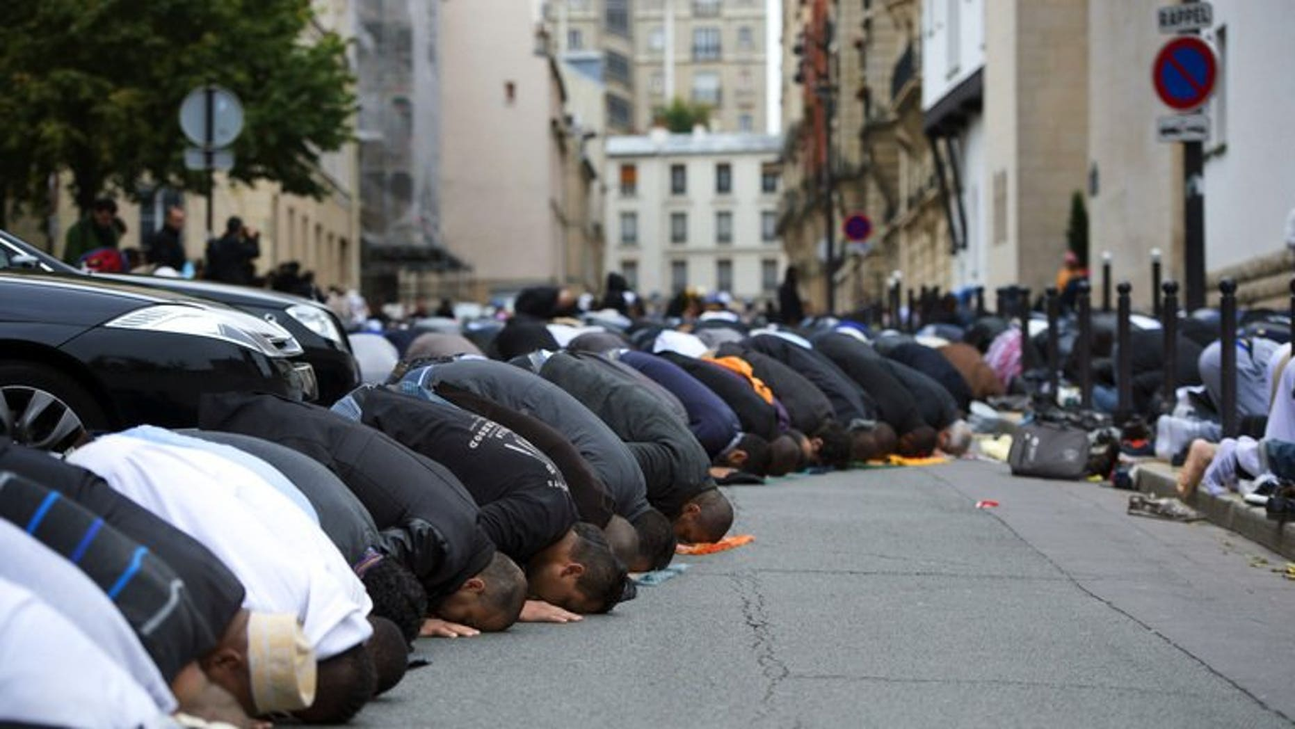 Muslims pray outside the Grande Mosque of Paris on the first day of Eid al-Adha on October 26, 2012.