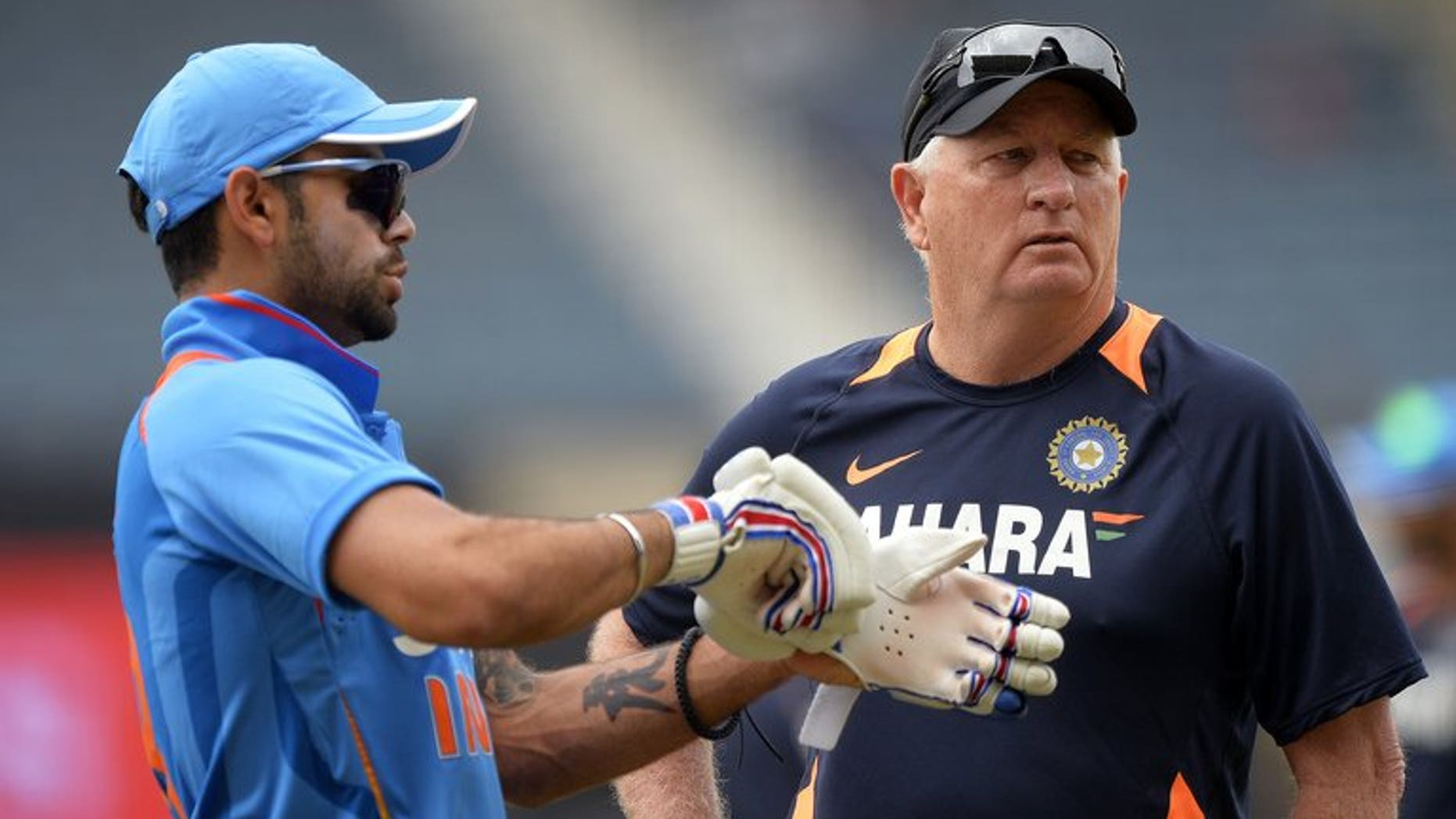 Indian captain Virat Kohli (left) confers with coach Duncan Fletcher before the start of the Tri-Nation one-day match against Sri Lanka at the Sabina Park stadium in Kingston, on July 2, 2013. Indian won the toss and elected to field.