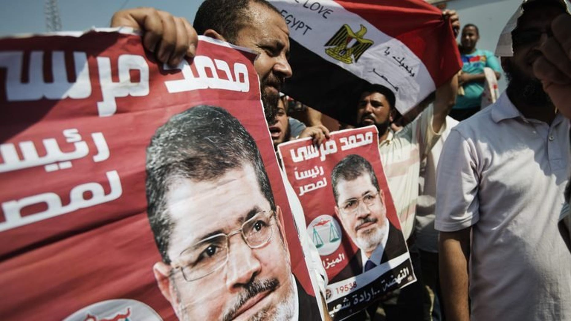 Protesters hold posters of Egyptian President Mohammed Morsi as Muslim Brotherhood members and Morsi's supporters gather outside in Cairo's eastern Nasr City district on July 2, 2013. A top Muslim Brotherhood leader urged Egyptians to stand ready to sacrifice their lives to prevent a coup.