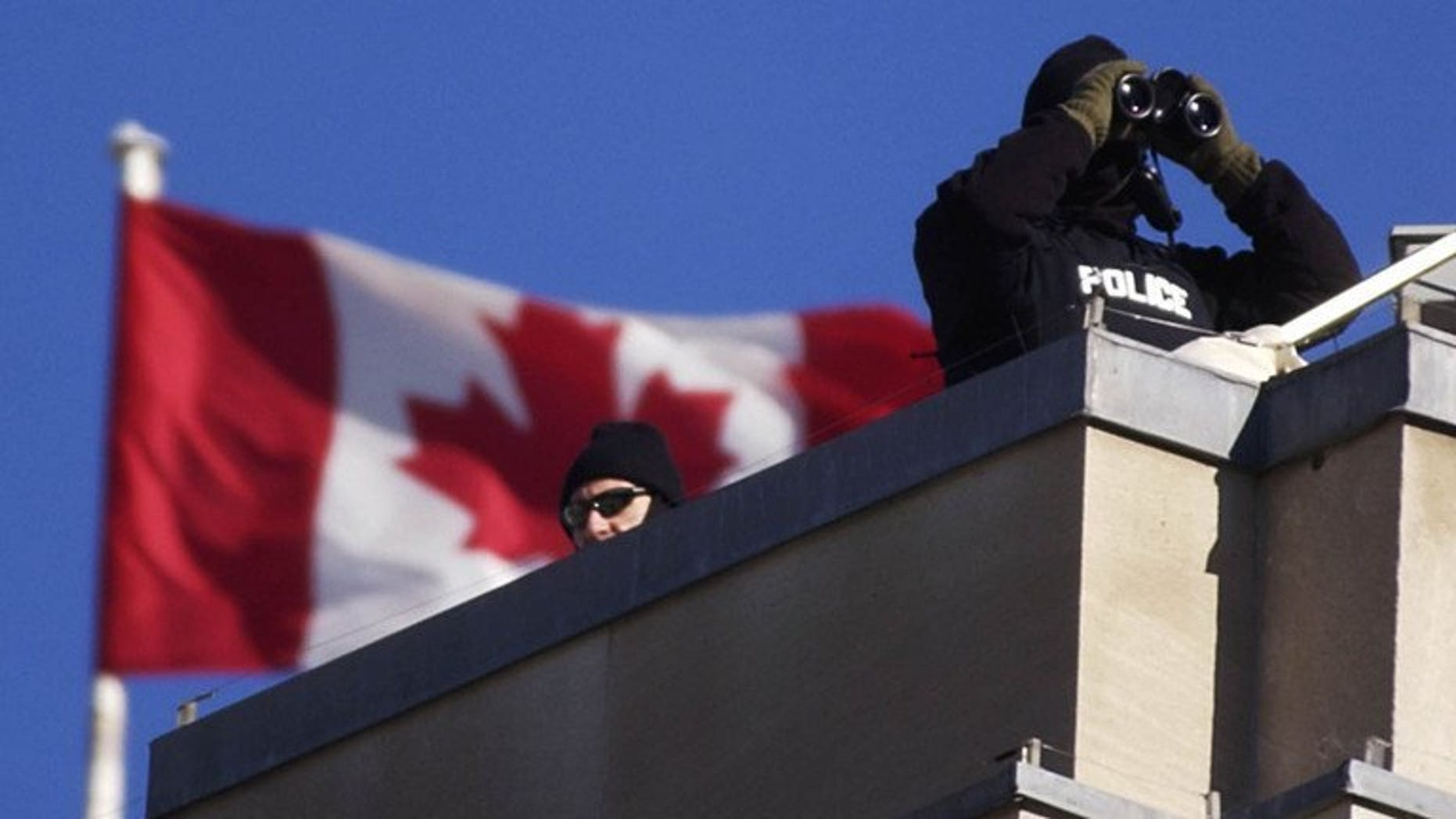 "Royal Canadian Mounted Police team keep watch from the roof of the Government Conference Center, November 16, 2001. Canadian police said Tuesday they had arrested two people ""inspired by Al-Qaeda"" who allegedly plotted to bomb the provincial legislature in western British Columbia."