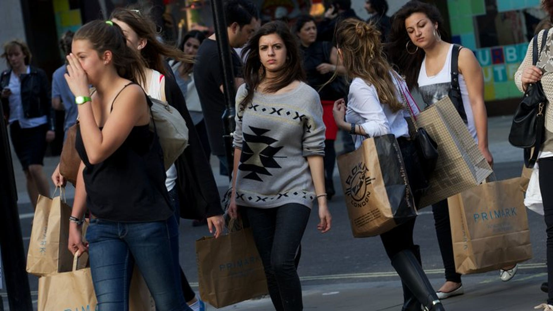 """Shoppers walk along Oxford Street on April 25, 2013. Britain faces a """"20-year generational battle"""" to restore financial stability and """"at least"""" four more years of austerity measures, the country's top civil servant warned Tuesday."""