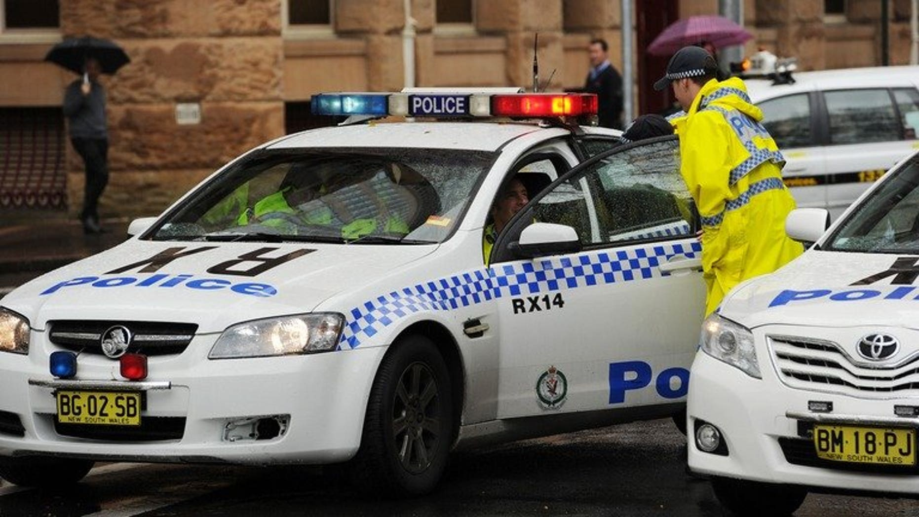 "Australian police block off one end of a city street on June 13, 2012. Police described as ""extremely depraved"" the case of a six-year-old boy obtained by his gay male parents via a surrogate and then sexually abused by them and others."