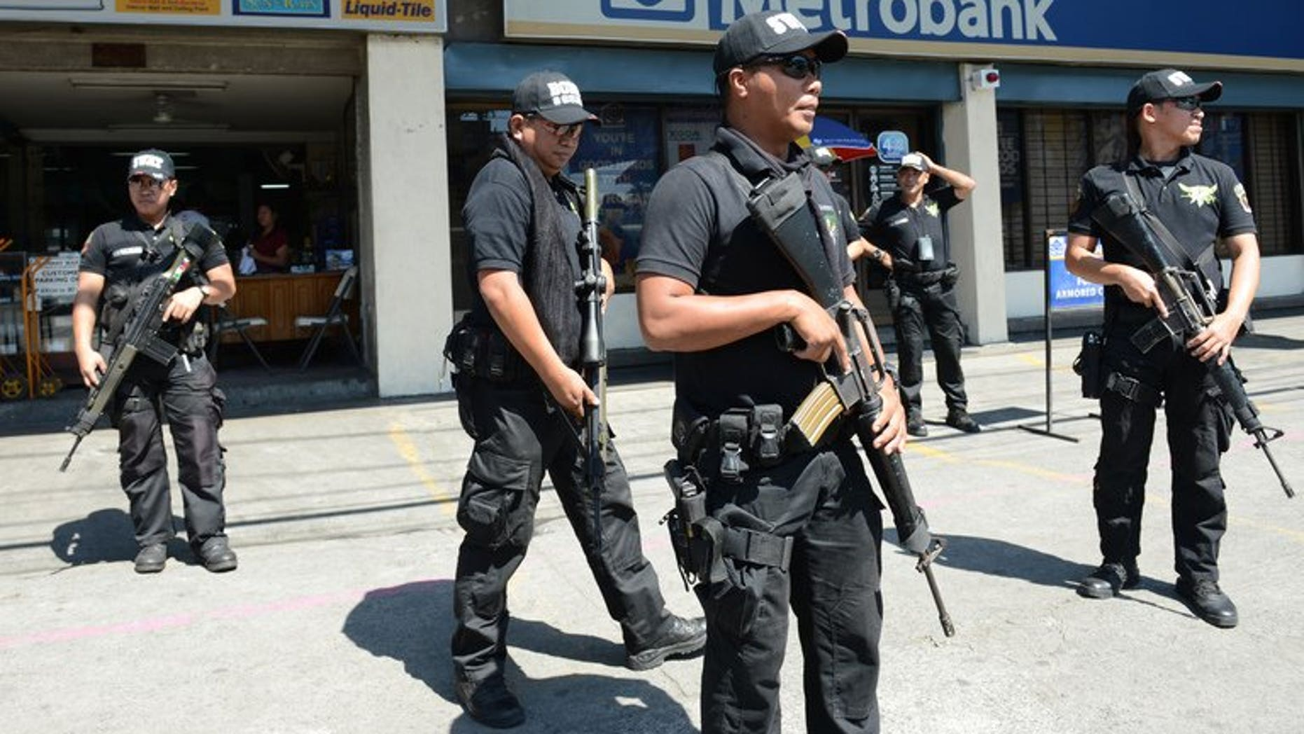 Members of the Pasay City SWAT team patrol in front of a bank in Manila on February 1, 2013. Five young men were shot dead before dawn on Wednesday in a street on the outskirts of the Philippines' main business district, police said.