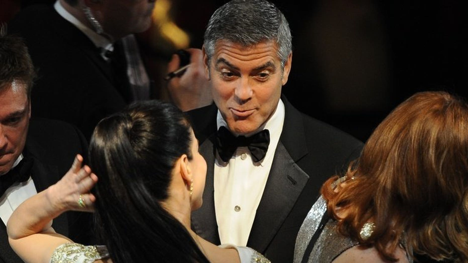 """US actor George Clooney talks to actress Sandra Bullock (C) prior to the 84th Annual Academy Awards in Hollywood, California on February 26, 2012. Hollywood heavyweights Bullock and Clooney will open the Venice film festival next month with their new movie """"Gravity"""" where they play two astronauts on an ill-fated mission."""