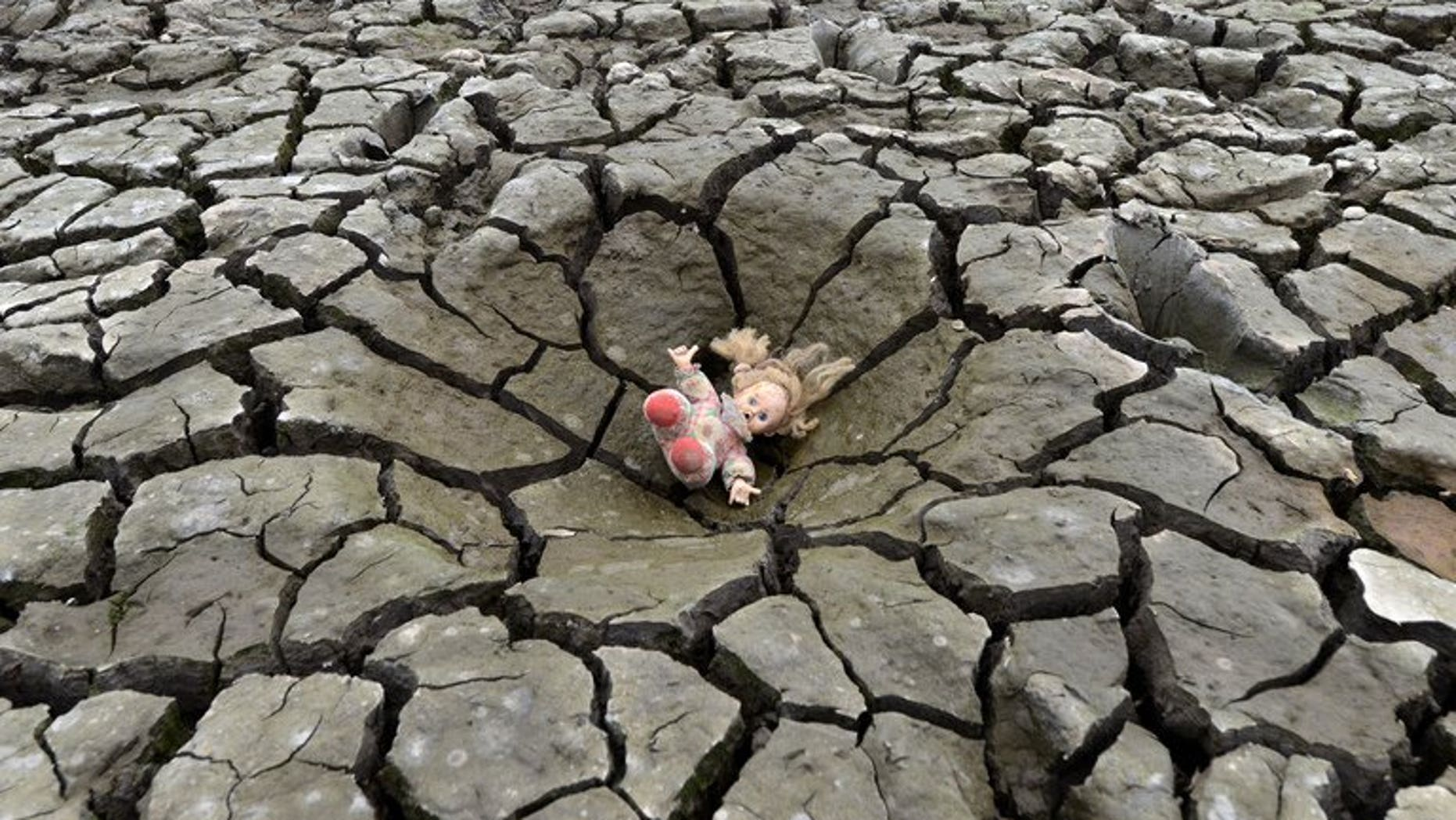 A doll lies on a hole in the dry soil of Los Laureles dam, southern Tegucigalpa, in Honduras on May 22, 2013. The first decade of the 21st century was the hottest on record, marked by unprecedented climate and weather extremes that killed more than 370,000 people, the United Nations weather agency said Wednesday.