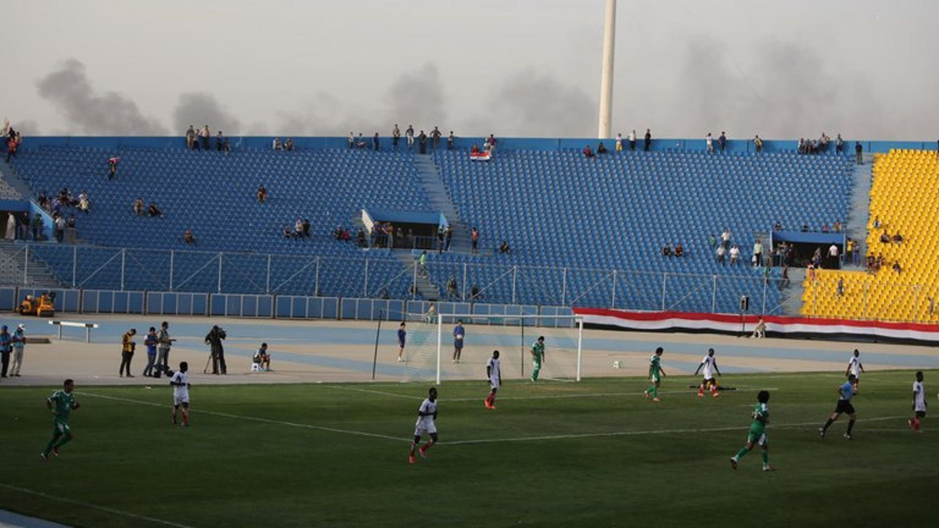 Smoke from explosions billow on the background as Iraq plays a friendly match against Liberia at al-Shaab Stadium in Baghdad on May 27, 2013. FIFA on Wednesday barred Iraq from hosting international football friendlies due to a massive surge in nationwide violence, barely three months after world football's governing body gave Baghdad the go-ahead.