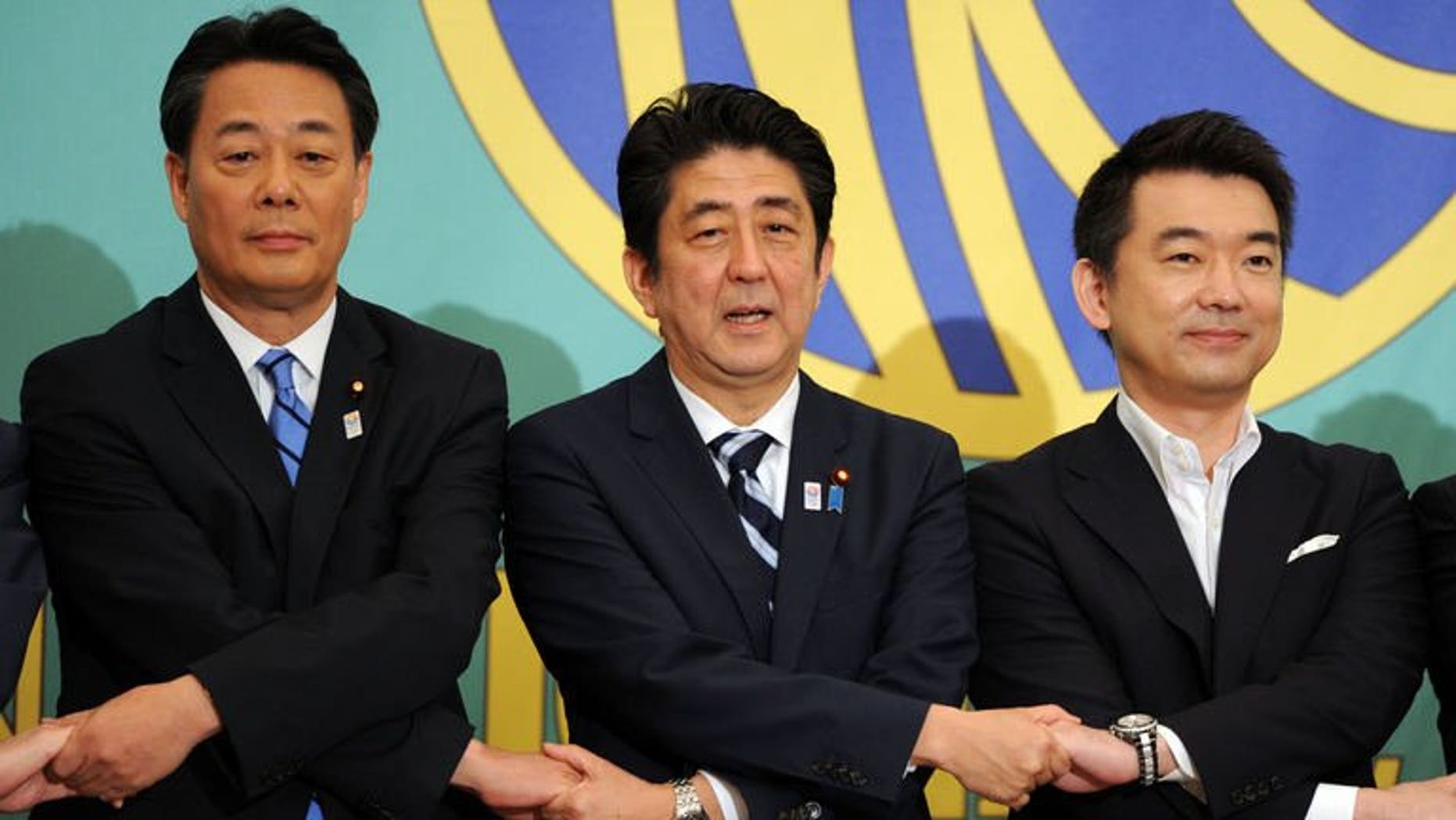 Japanese Prime Minister and ruling Liberal Democratic Party (LDP) leader Shinzo Abe (C) shakes hands with Democratic Party of Japan (DPJ) leader Banri Kaieda (L) and co-leader of Japan Restoration Party Toru Hashimoto prior to their political debate in Tokyo on July 3, 2013. Campaigning begins Thursday in an election expected to give Abe an almost unbeatable hand.