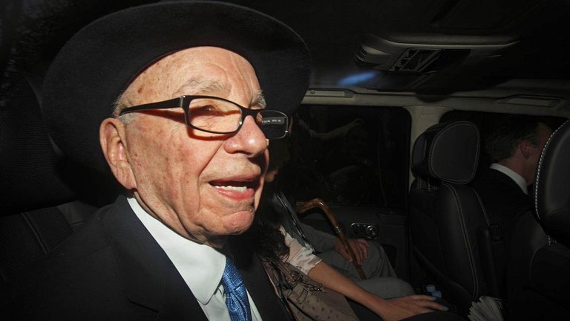 """Rupert Murdoch is seen in a car in central London on April 26, 2012. The News Corp chief called the police investigation into his News International journalists a """"disgrace"""" in a secret recording of talks with staff from the Sun newspaper, aired on British television."""