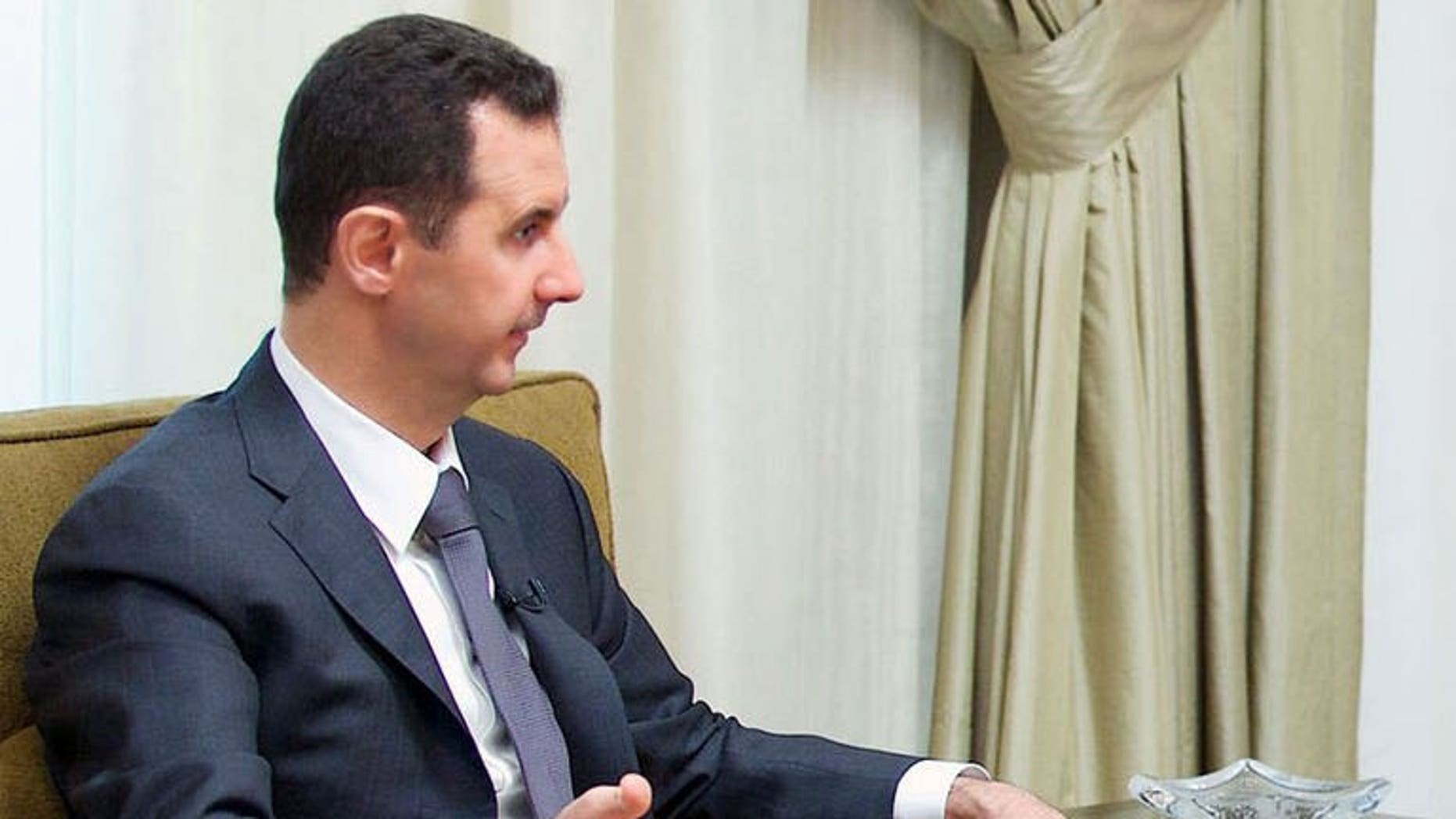 """A handout picture released by the Syrian Arab News Agency (SANA) shows President Bashar al-Assad giving an interview to a local newspaper in Damascus, on July 2, 2013. Assad has accused the West of sending """"takfiri terrorist groups"""" to his country as a way to get rid of them, in an interview with a Syrian daily."""