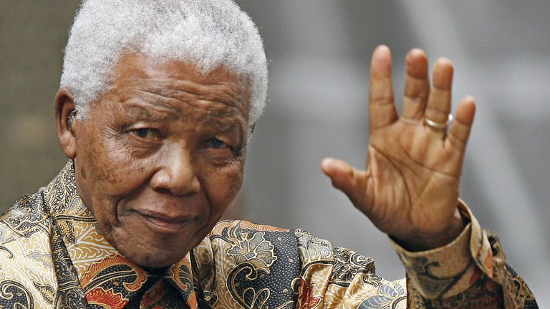 """Nelson Mandela waves to the media as he arrives outside No 10 Downing Street in central London, on August 28, 2007. Doctors treating Mandela said that he was in a """"permanent vegetative state"""" and advised his family to turn off his life support machine, according to court documents dated June 26, obtained by AFP."""
