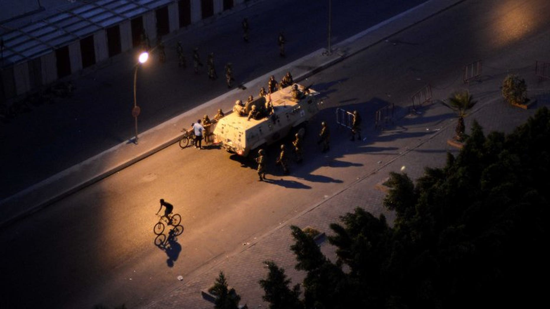 "An Egyptian army armored personnel carrier and soldiers are stationed on a street in Cairo following the toppling of ousted Egyptian president Mohamed Morsi on July 4, 2013. An alliance of Islamist parties and movements including ousted president Mohamed Morsi's Muslim Brotherhood has called for ""peaceful protests"" on Friday to denounce the military's overthrow of the Islamist president."