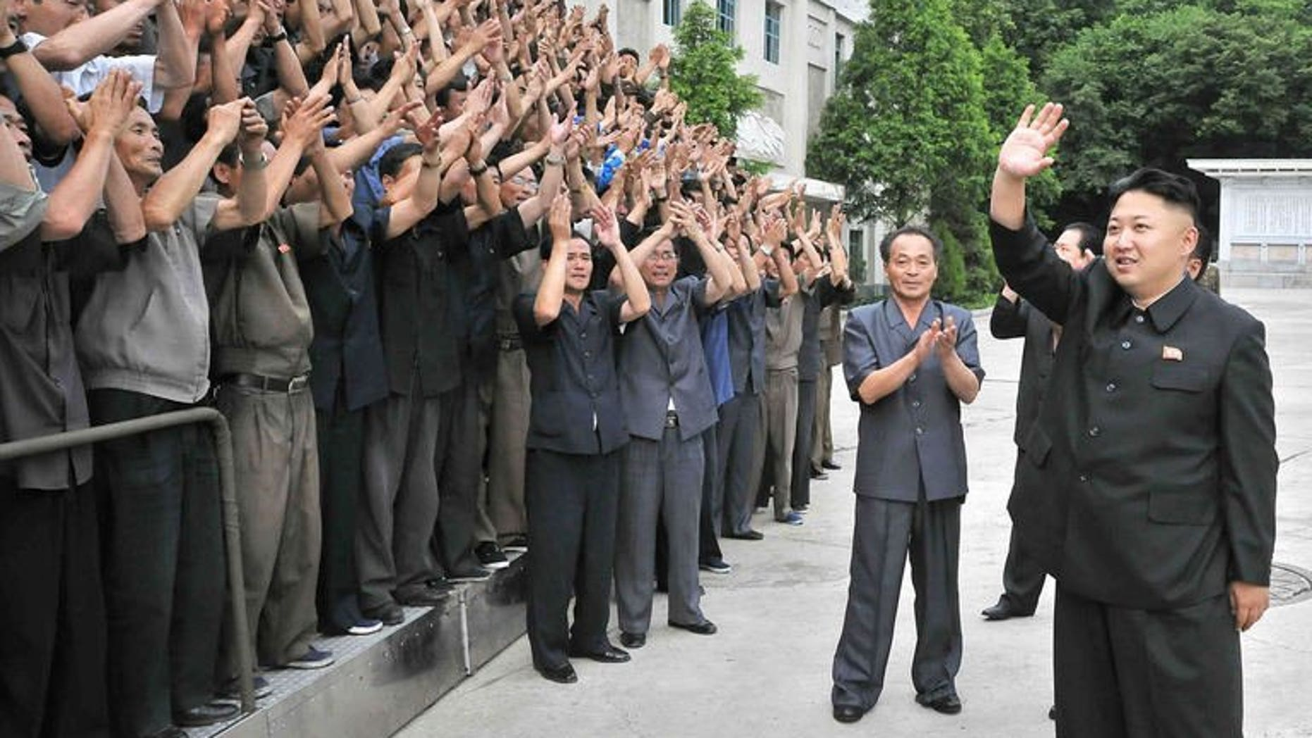 """North Korean leader Kim Jong-Un waves to employees at the Kongdong Precision Machine Plant in Pyongyang, in a photo released by North Korea's official Korean Central News Agency on July 5, 2013. Russia said Friday it still had """"a number of substantial"""" differences with North Korea concerning efforts to resume stalled six-party negotiations on the Stalinist state's nuclear weapons drive."""