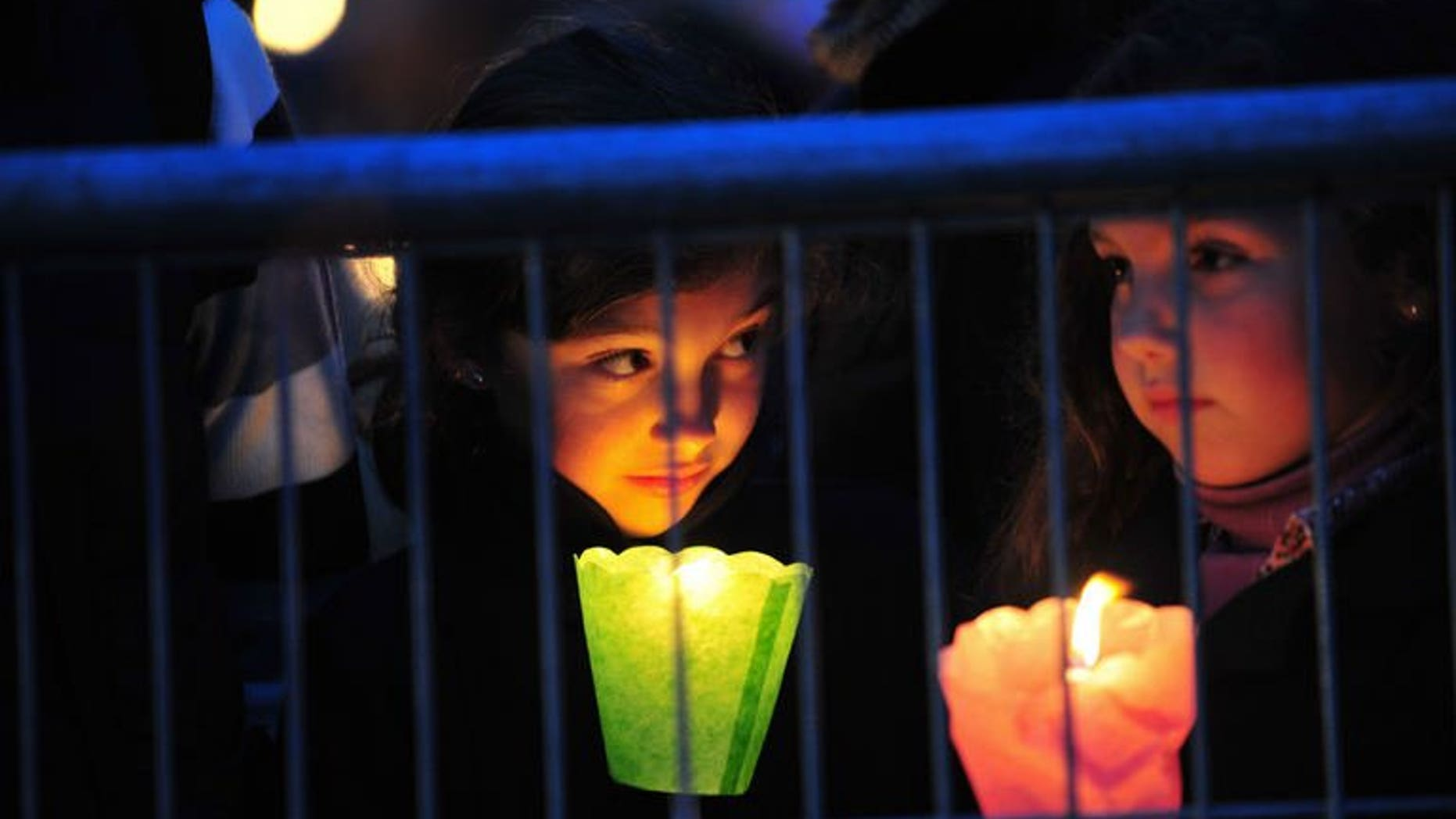 Children hold candles during a prayer vigil at the ancient Circus Maximus Arena in Rome on April 30, 2011, on the eve of the beatification of the late Pope John Paul II. Late popes John Paul II and John XXIII will be made saints of the Roman Catholic Church, the Vatican said on Friday in a widely-awaited announcement, without specifying when the canonisations will occur.