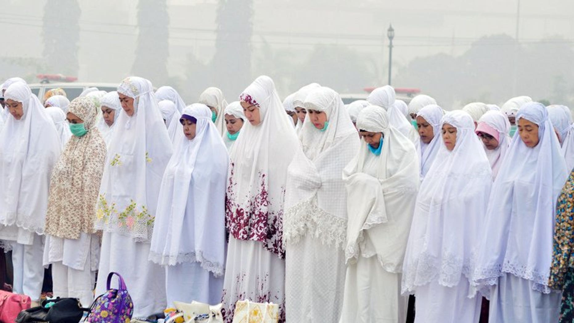 Indonesian Muslim women take part in mass prayers asking for rain at a square covered by thick haze in Dumai on June 25, 2013. Sales and distribution of alcohol could be banned in some parts of Indonesia after Muslim hardliners won a Supreme Court victory, an official said Friday.