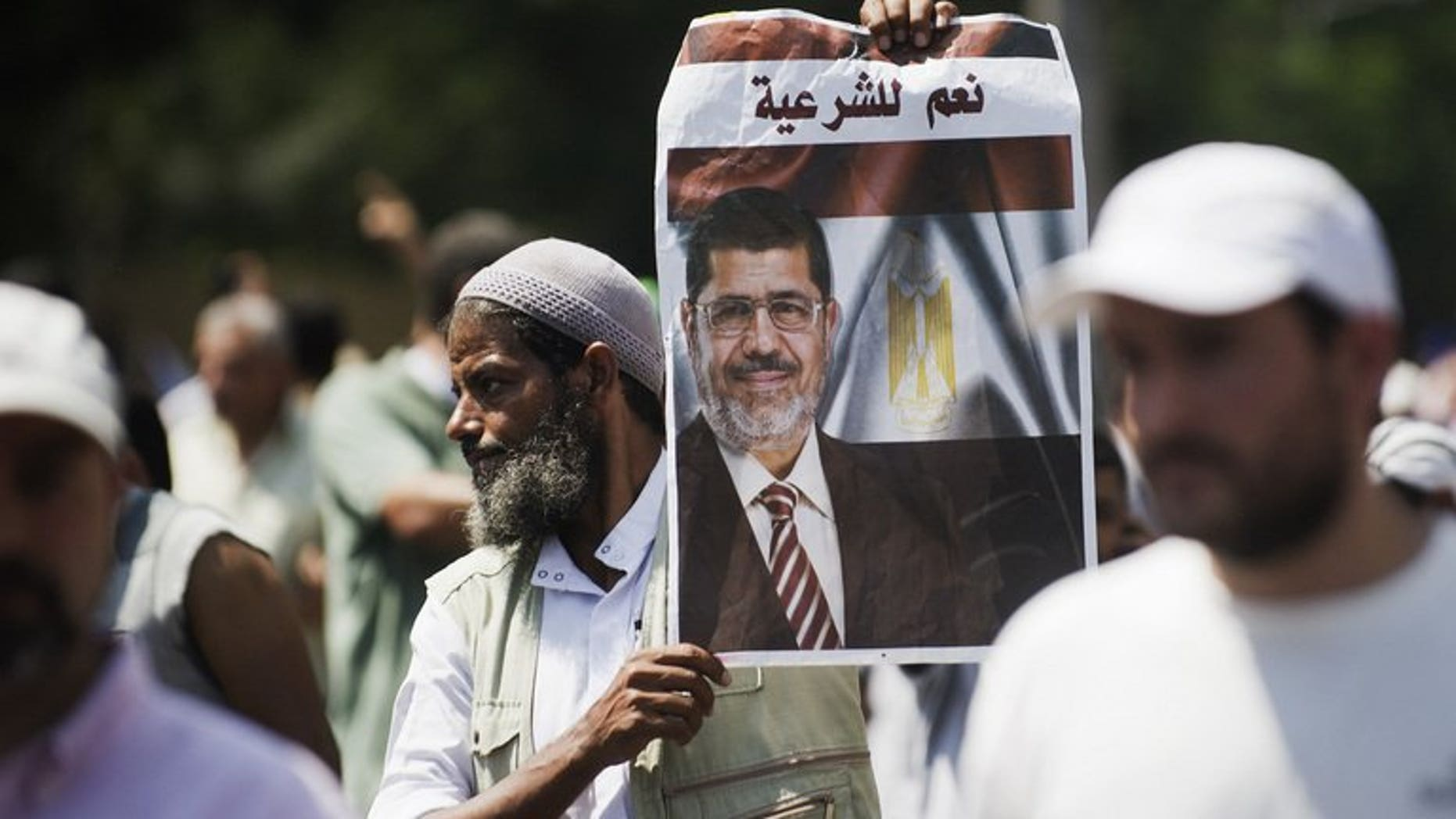 """A supporter of the Muslim Brotherhood and ousted Egyptian president Mohamed Morsi holds his portrait with text on it reading in Arabic: """"Yes to Sharia"""" as they march near Cairo University on July 5, 2013. Gunfire erupted outside the Cairo headquarters of the Republican Guard on Friday where supporters of ousted Egyptian president Mohamed Morsi had massed vowing to defend him."""