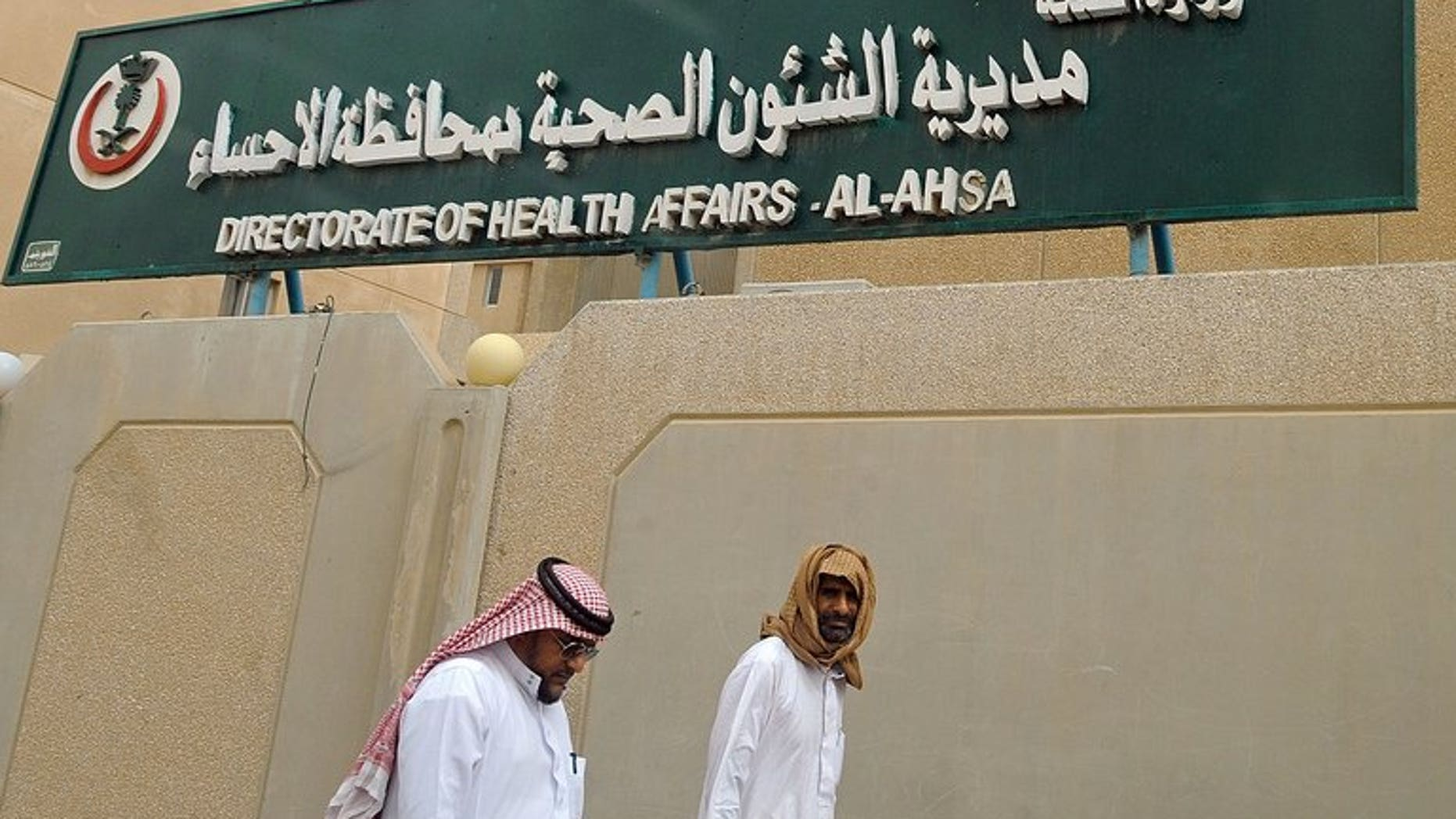 Saudi men walk to the King Fahad hospital in the city of Hofuf, east of the capital Riyadh on June 16, 2013. The World Health Organization announced it had convened emergency talks on the deadly MERS virus, but said the move did not mean it was hiking its global alert level.