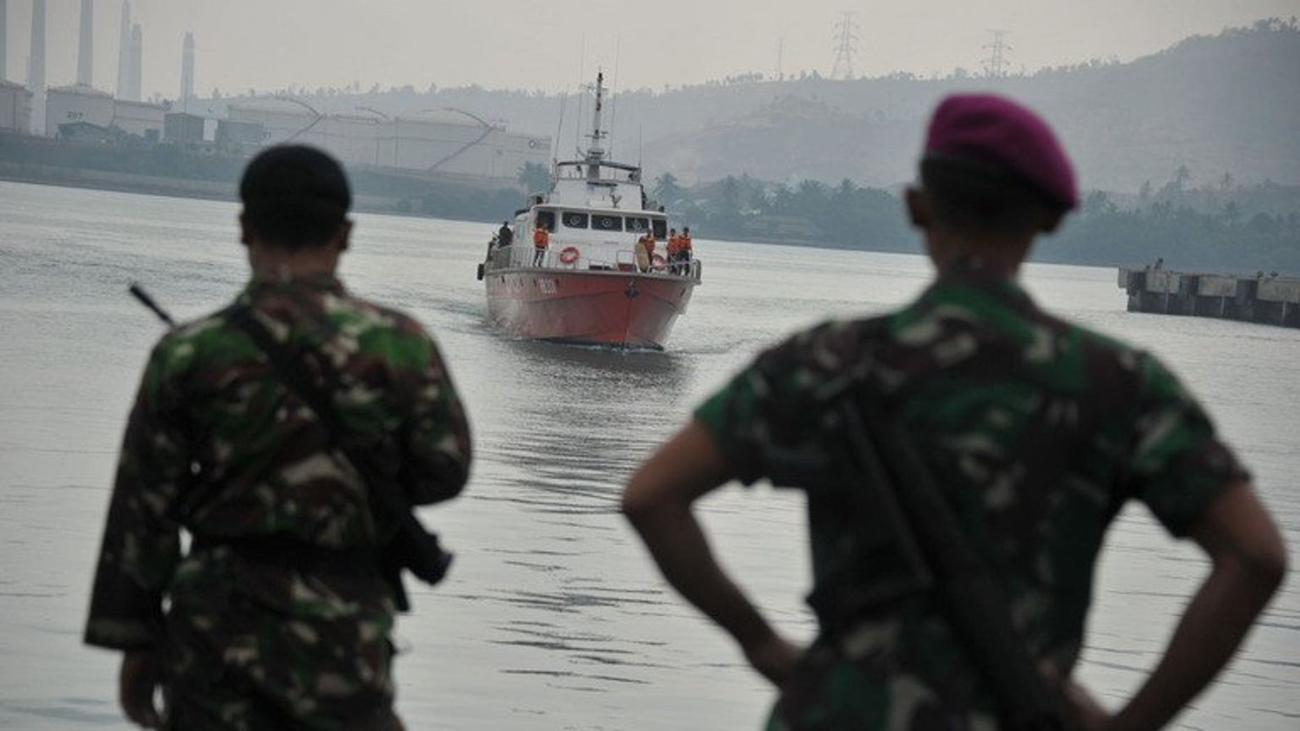 Indonesian marines look towards a rescue boat carrying asylum-seekers at Merak seaport on August 31, 2012. A people-smuggling boat carrying about 80 asylum-seekers broke down in seas south of Indonesia on Friday, prompting several vessels to divert in a bid to help it, Australian and Indonesian officials said.