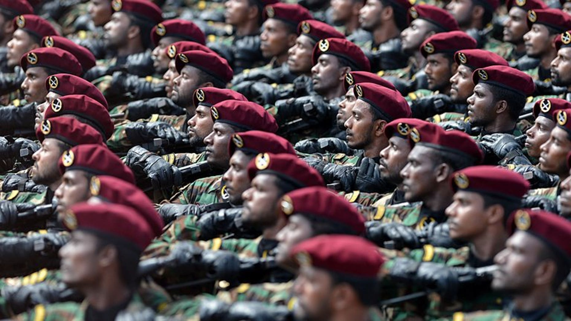 Sri Lankan commandos march during a Victory Day parade in Colombo on May 18, 2013. Sri Lanka's police arrested 12 commandos in connection with the execution-style killing of five students during the island's Tamil separatist war, an official said Friday.
