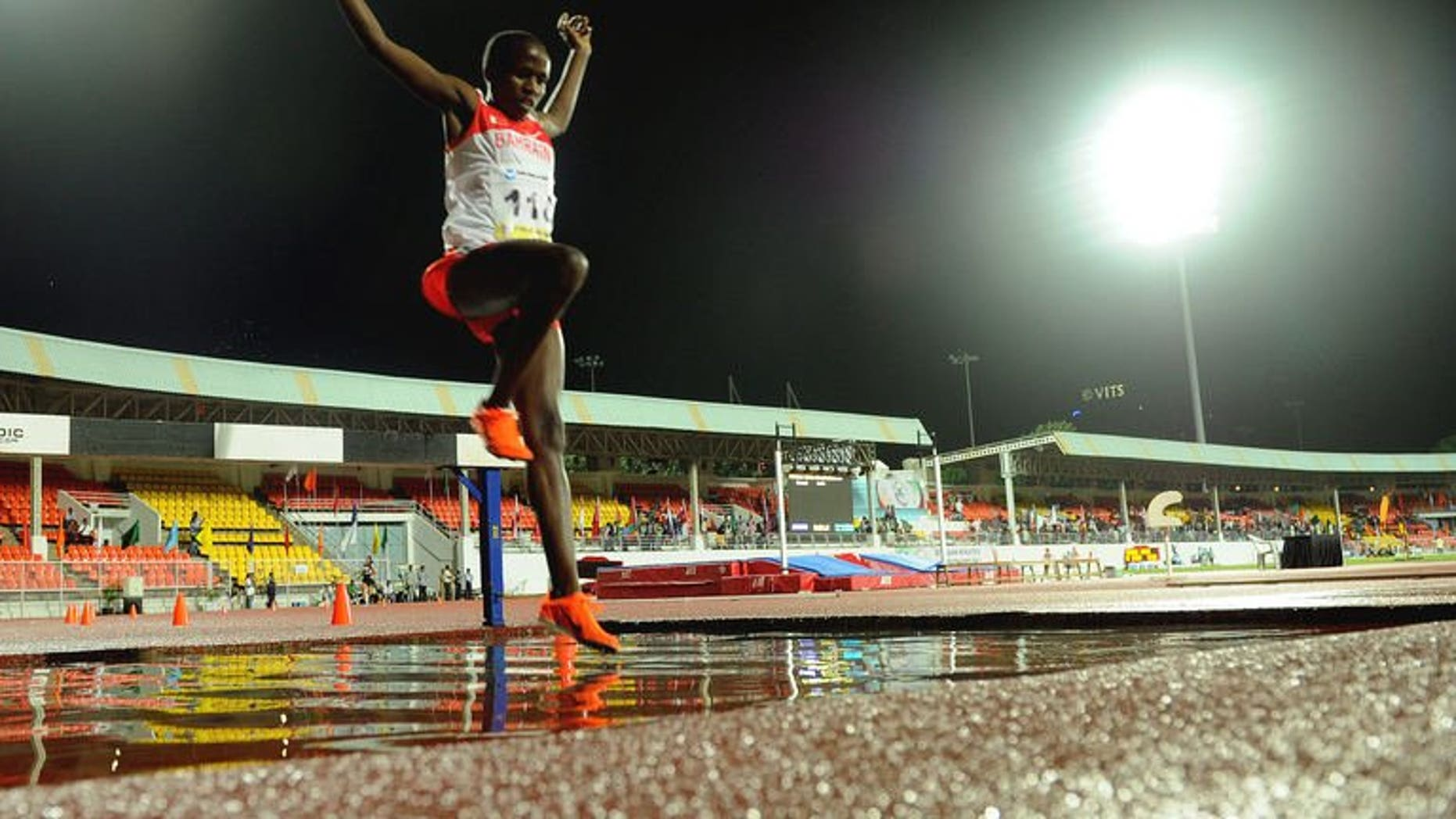 Ruth Jebet leaps over a puddle in the women's 3000 meters steeplechase during the third day of the five-day Asian Athletics Championship 2013 at the Chatrapati Shivaji Stadium in Pune on July 5, 2013.