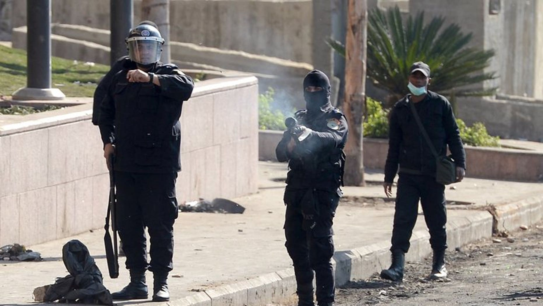 Egyptian riot police fires a tear gas canister towards protesters on January 29, 2013. Unidentified gunmen killed two Egyptian policemen guarding a government building in the northern Sinai town of Al-Arish, a security official told AFP.