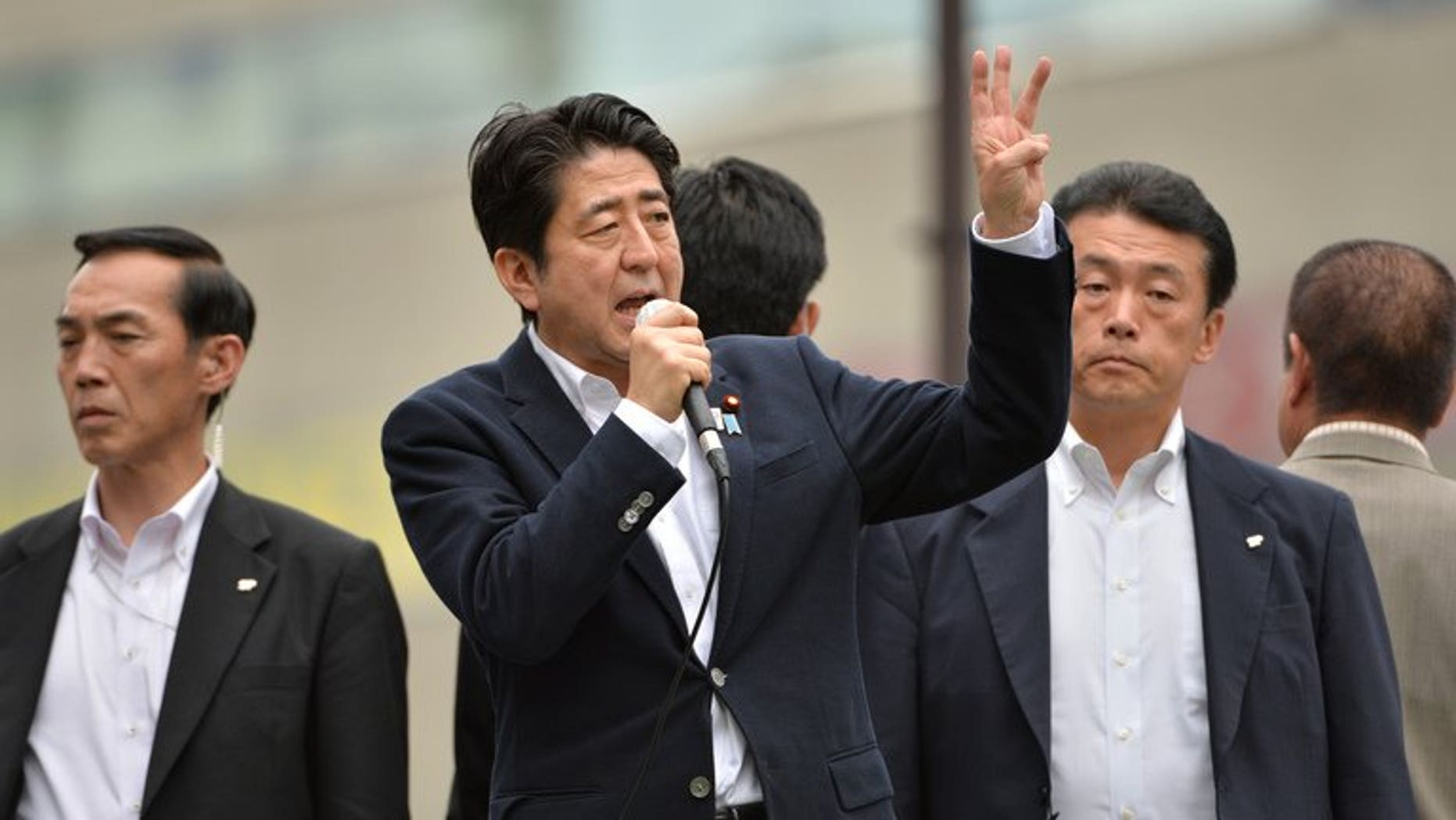 Japan's Prime Minister Shinzo Abe (C) delivers an election campaign speech in Tokyo's Ikebukuro, on July 4, 2013. Abe's ruling bloc is set to secure a majority in the upper house in this month's election, according to newspaper polls.