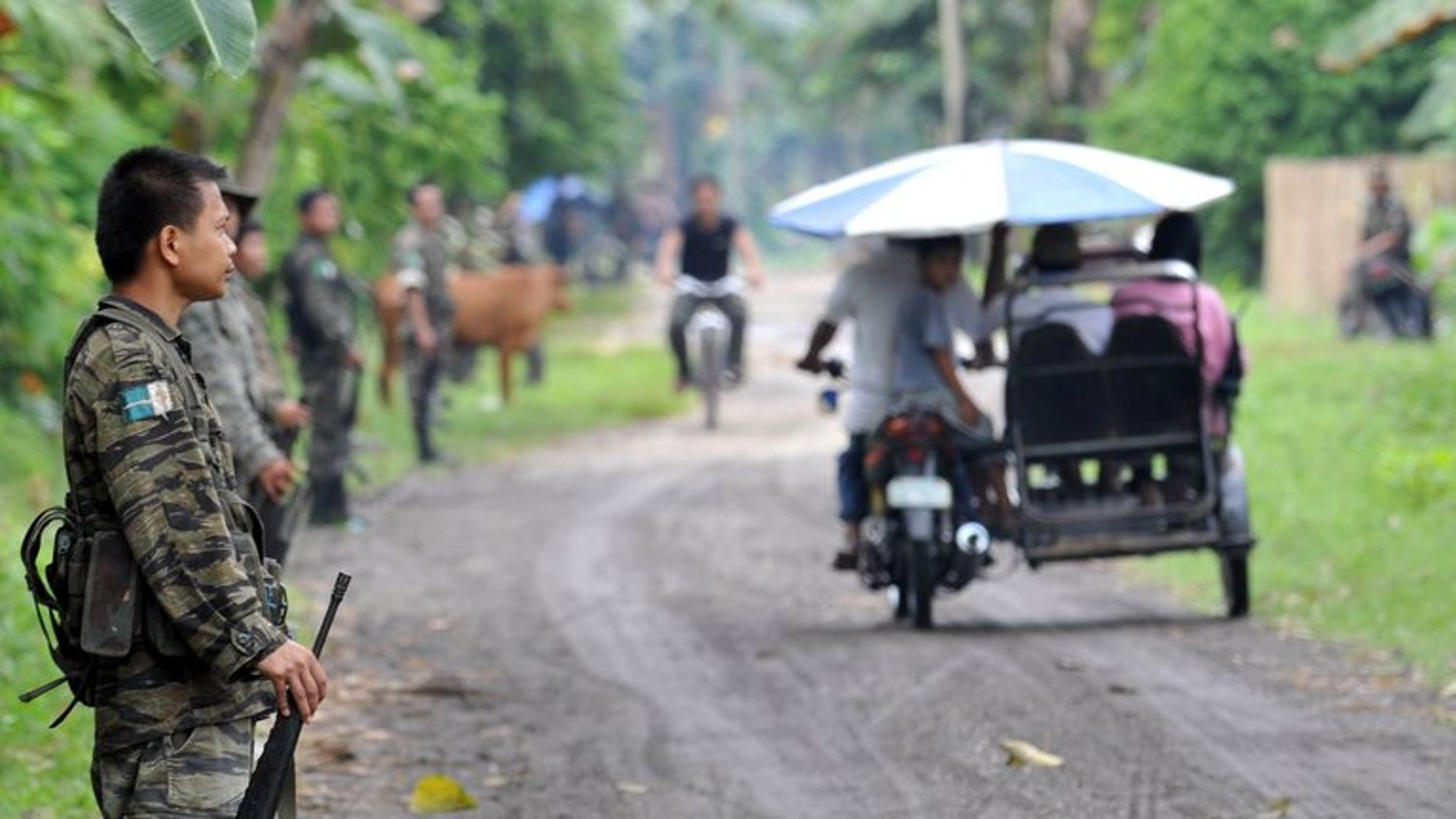 This file photo shows members of the southern Philippine rebel group, the Moro Islamic Liberation Front (MILF), lining a street as villagers pass by, in a town on Mindanao island, on September 19, 2009. The United States has warned Americans against travel to the southern Philippines just days after Australia and Canada issued similar advice.
