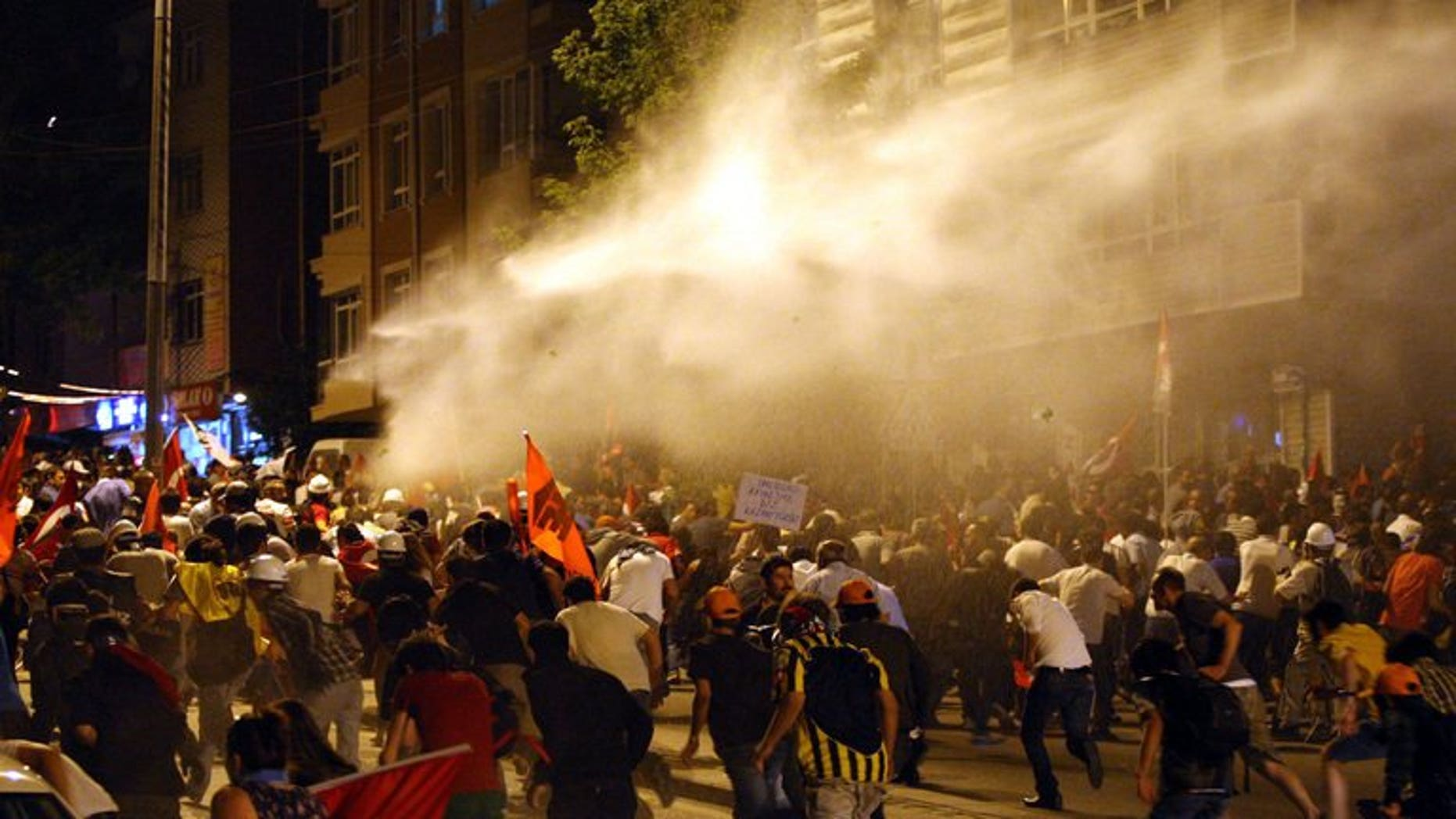 Protesters take cover from water cannon during clashes with police in Ankara on June 25, 2013. The Council of Europe's human rights commissioner Nils Muiznieks has urged an investigation into the use of excessive police force during a crackdown on anti-government protests in Turkey last month.