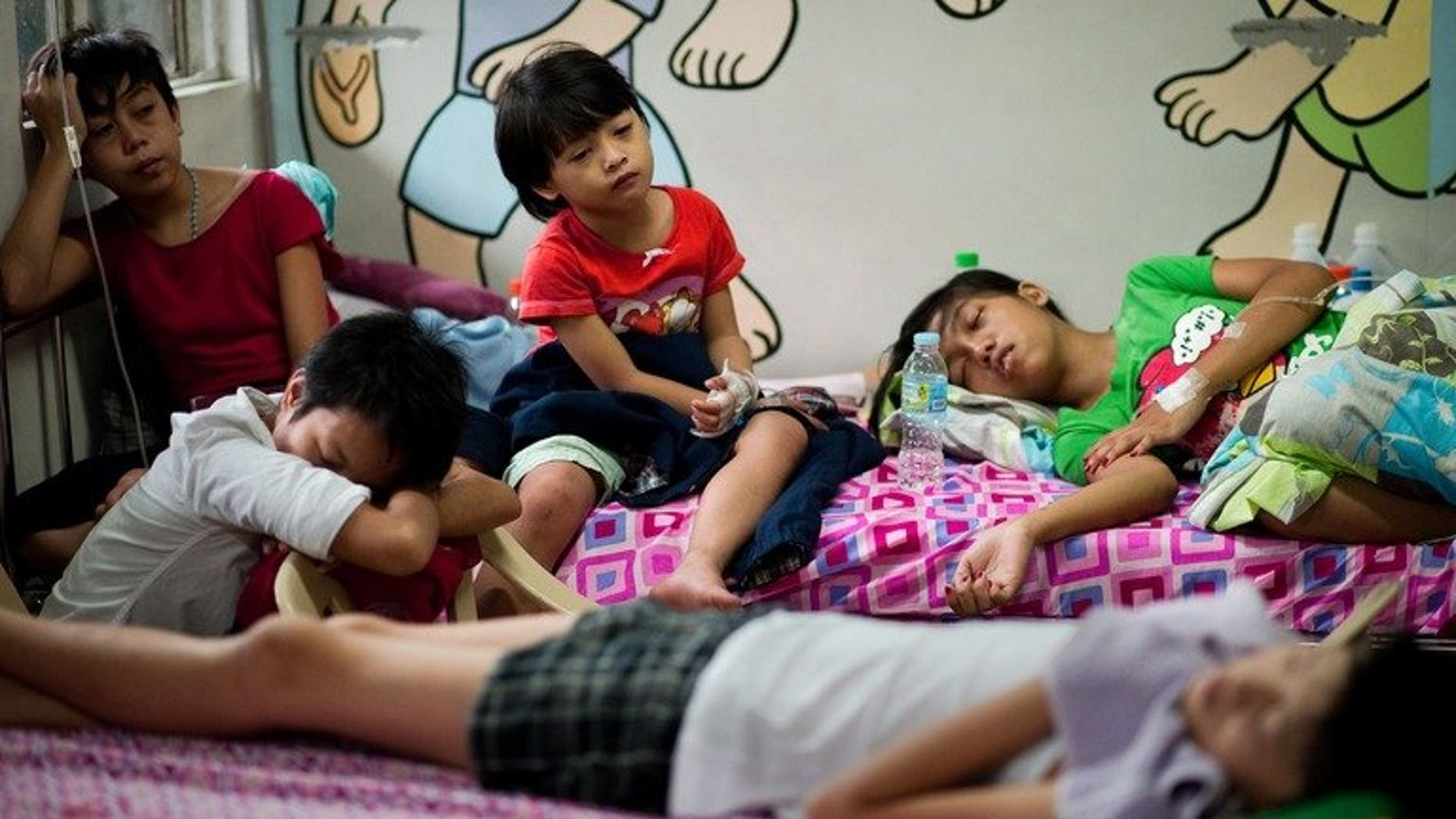 Patients with dengue fever share beds at a hospital in Quezon city, in the suburbs of Manila, on August 14, 2012. Dengue fever has surged in the central Philippines, infecting more than 1,800 people and killing at least ten, a provincial official says.