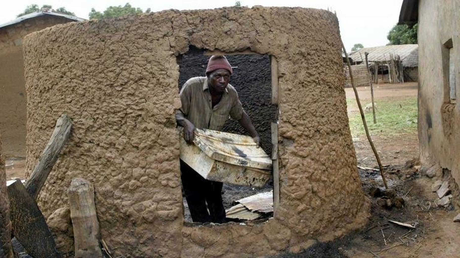 Monday Longshak in his burnt mud house at Sabon Gida in Quanpan district in May 2004 after a raid by Fulani herdsmen. Gunmen suspected to be ethnic Fulani herdsmen invaded a farming village in restive central Nigeria's Benue State, burning several houses, police said Saturday, amid reports that at least 20 people died in the violence.