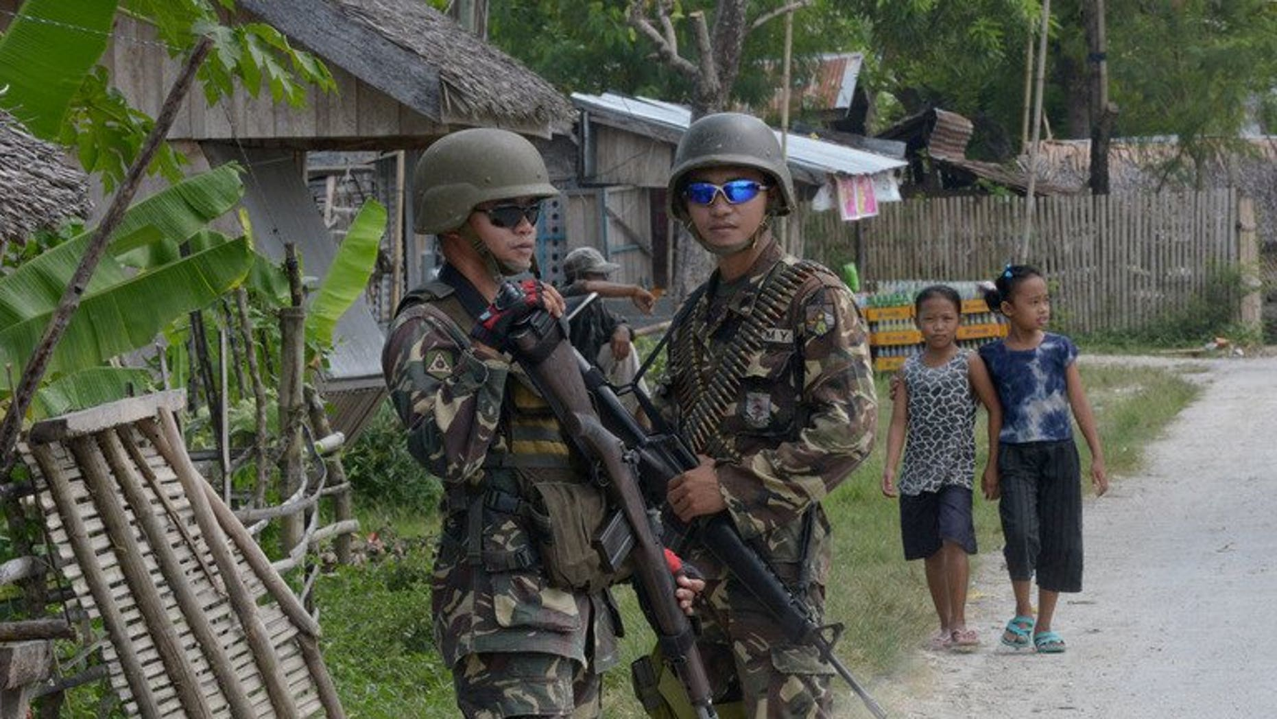 Soldiers guard a road in the Philippine town of Datu Salibo, on October 11, 2012. Communist insurgents have promised revenge after Philippine soldiers killed their regional spokesmen along with seven other rebels in the latest operation against the militants since talks to end one of Asia's longest running insurgencies collapsed.