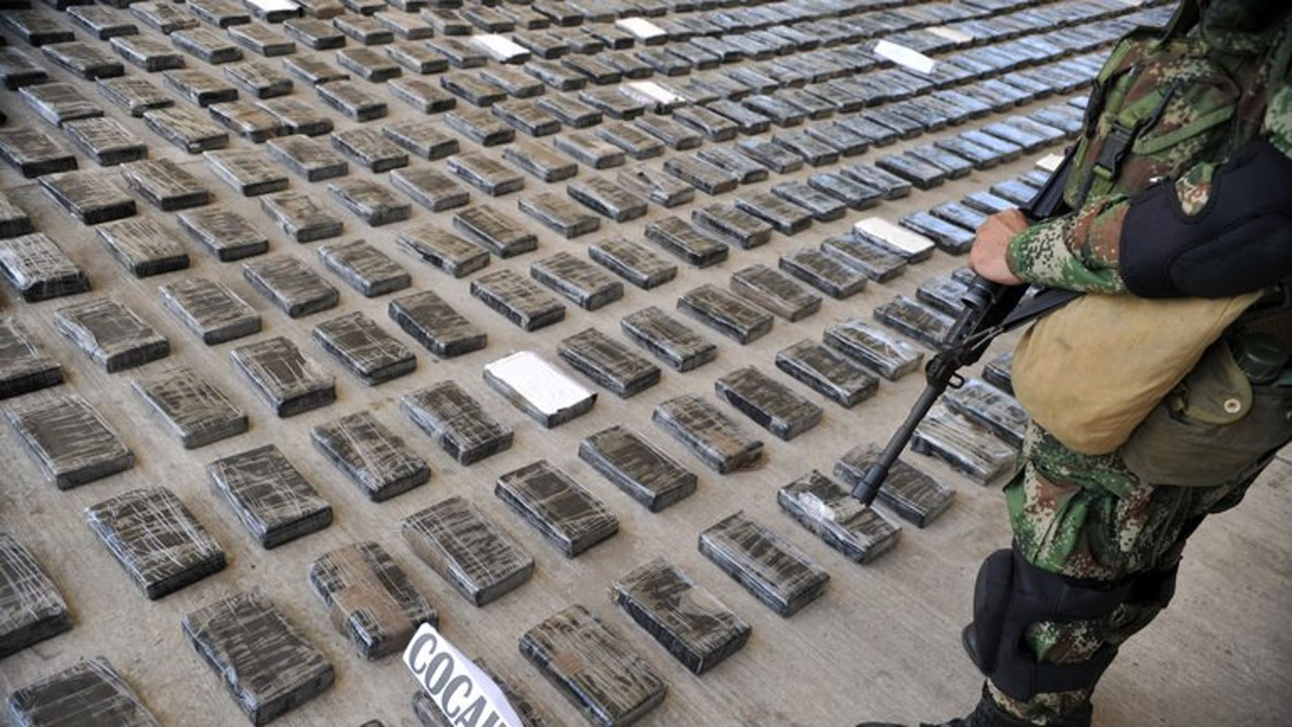 A soldier guards a huge shipment of cocaine seized in a clandestine laboratory, on March 16, 2013, in Tumaco, Colombia. An Italian mafia capo alleged to be the biggest cocaine trafficker in the world will be deported to Italy, a day after being arrested in a Colombian shopping mall, prosecutors said.