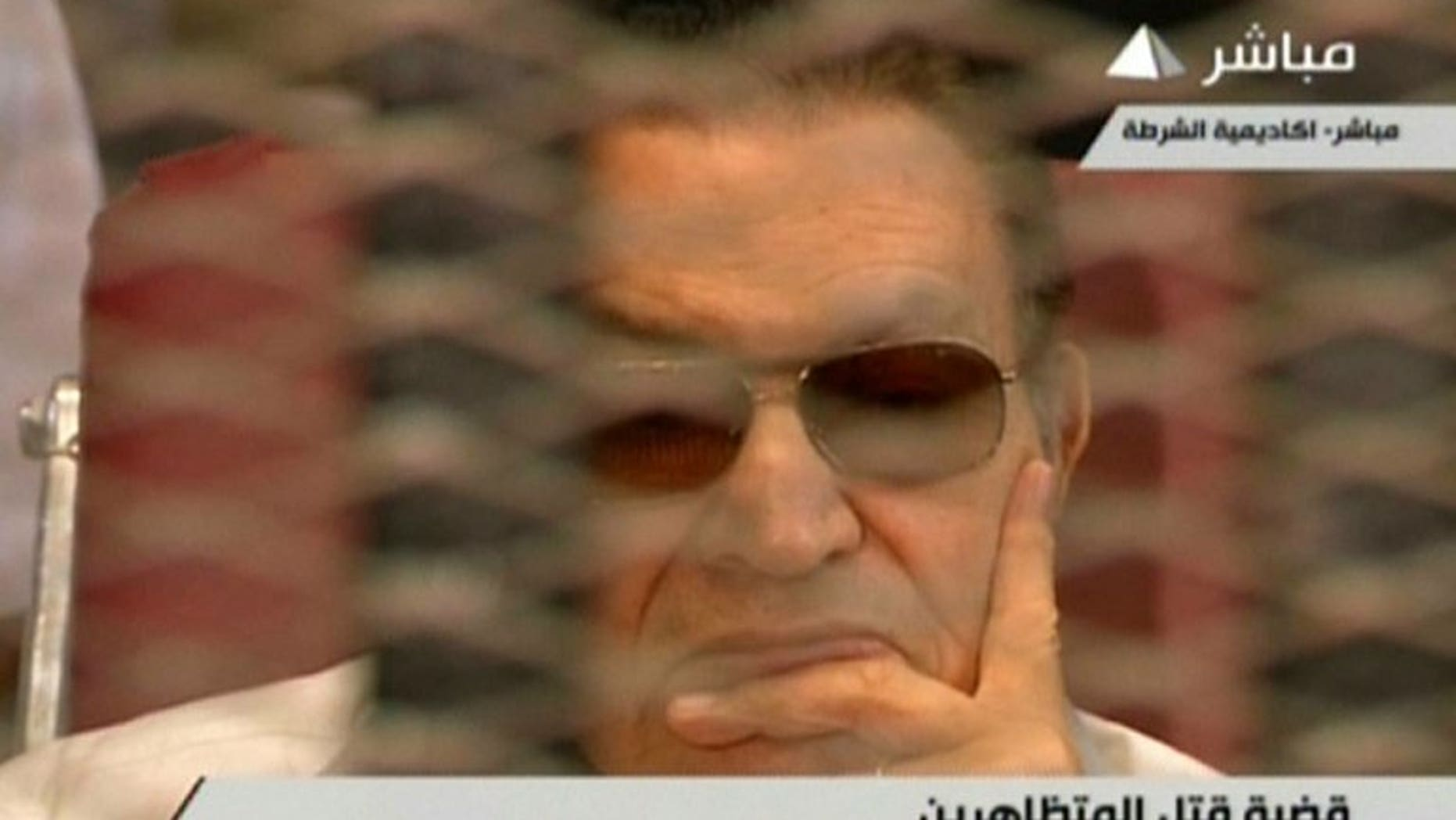 An image from Egyptian state TV shows ousted president Hosni Mubarak sitting behind bars during his retrial in Cairo on July 6, 2013.