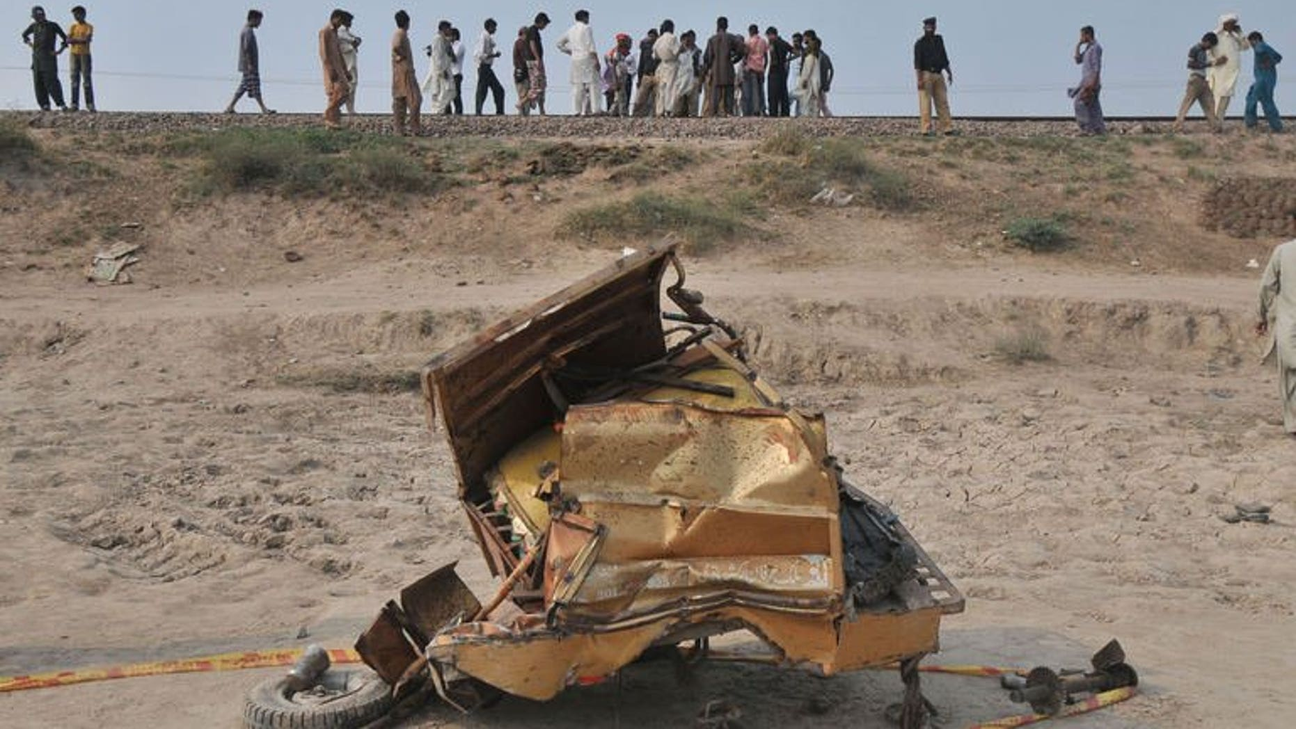 The mangled wreckage of a motorcycle rickshaw after a train collided with it in Khanpur town, Punjab province, on July 6, 2013. At least 14 people, including two children, were killed in the crash.