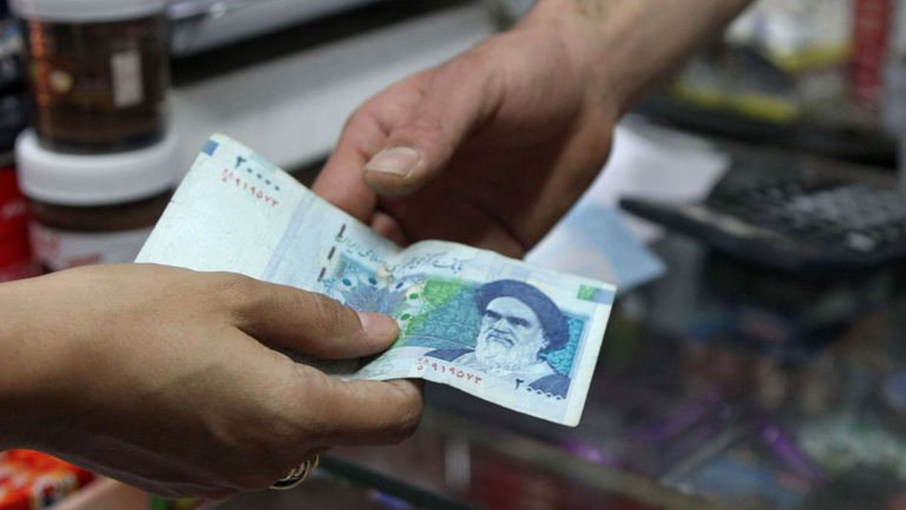 An Iranian woman pays with a 20000 rial banknote in Tehran on September 30, 2012. Iran's central bank on Saturday drastically devalued the national currency's fixed subsidised rate against the dollar, as the Islamic republic struggles to shore up its faltering economy.