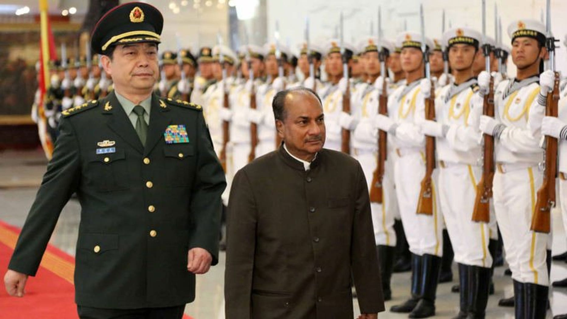 """Indian Defence Minister AK Antony (R) inspects a tri-Services guard of honour with his Chinese counterpart, General Chang Wanquan in Beijing on July 5, 2013. The Chinese and Indian defence chiefs agreed Saturday to strengthen """"peace and tranquility"""" along their frontier, state media reported, as the countries work to keep tensions in a disputed border area in check."""