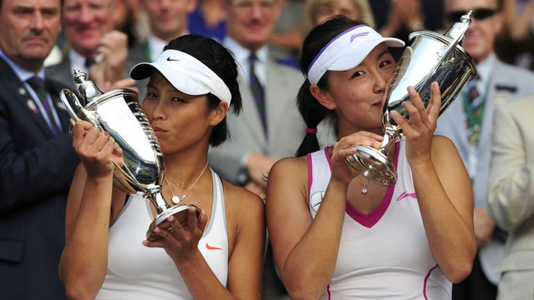 China's Peng Shuai (R) and Taiwan's Hsieh Su-Wei pose with the winners trophies after beating Australians Ashleigh Barty and Casey Dellacqua in the women's doubles final at the All England Club in Wimbledon, southwest London, on July 6, 2013. Peng and Hsieh won 7-6, 6-1.