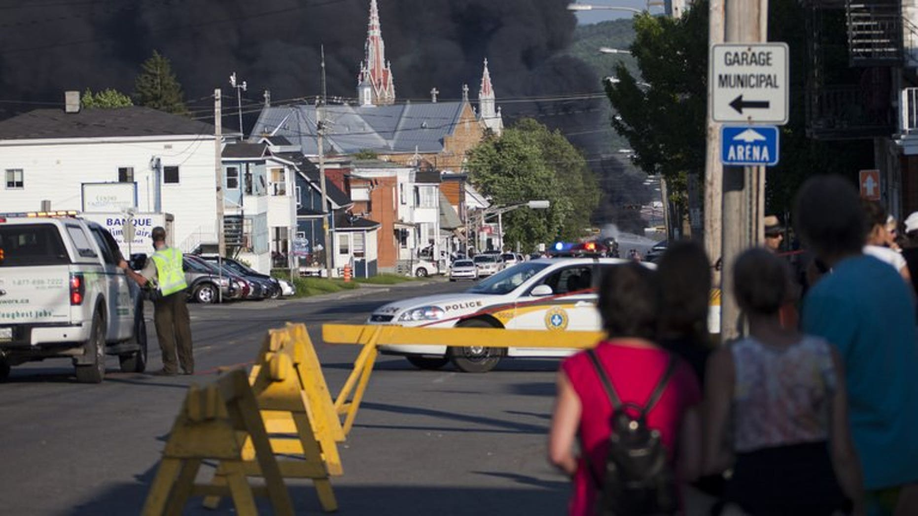 Residents watch rising smoke after a freight train loaded with oil derailed in Lac-Megantic in Canada's Quebec province on June 6, 2013. At least 80 people are missing in the small Canadian town after the accident, a firefighter told AFP.