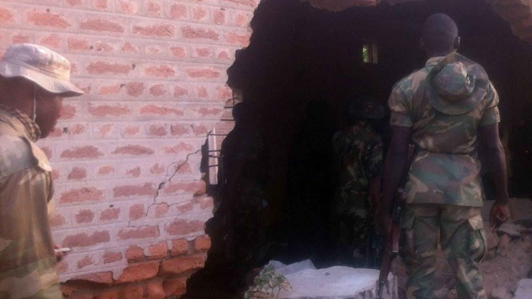A soldier stands in front of a damaged wall at a prison after an attack in the northeastern town of Bama, on May 7, 2013. Nigeria's northeastern Yobe state on Sunday ordered the closure of all secondary schools after an incident that saw suspected Islamist extremists kill 42 people in a gun and bomb attack on a boarding school.