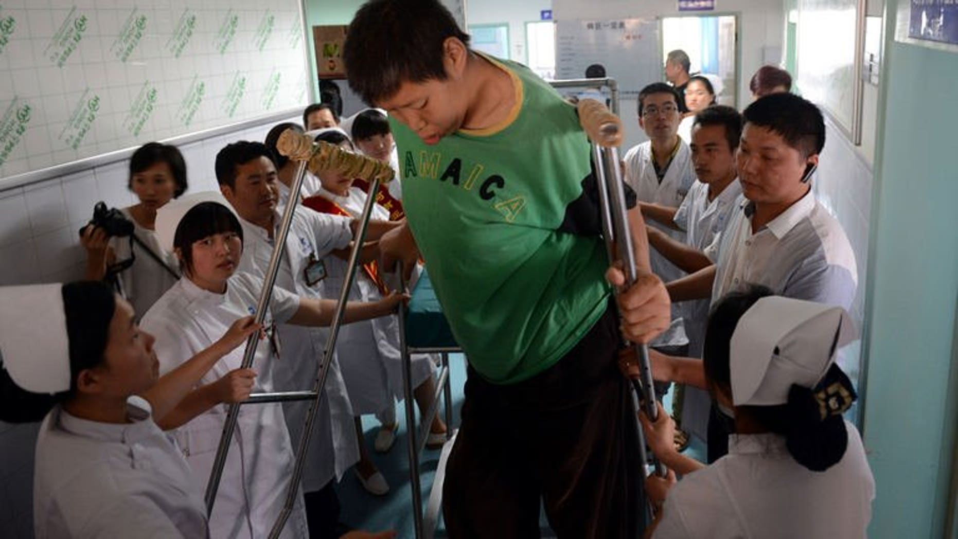 Wang Fengjun gets off a specially designed chair at a hospital in Zhengzhou, central China, on July 6, 2013. Wang, who is among the world's tallest living people, has been hospitalised for a hip replacement.