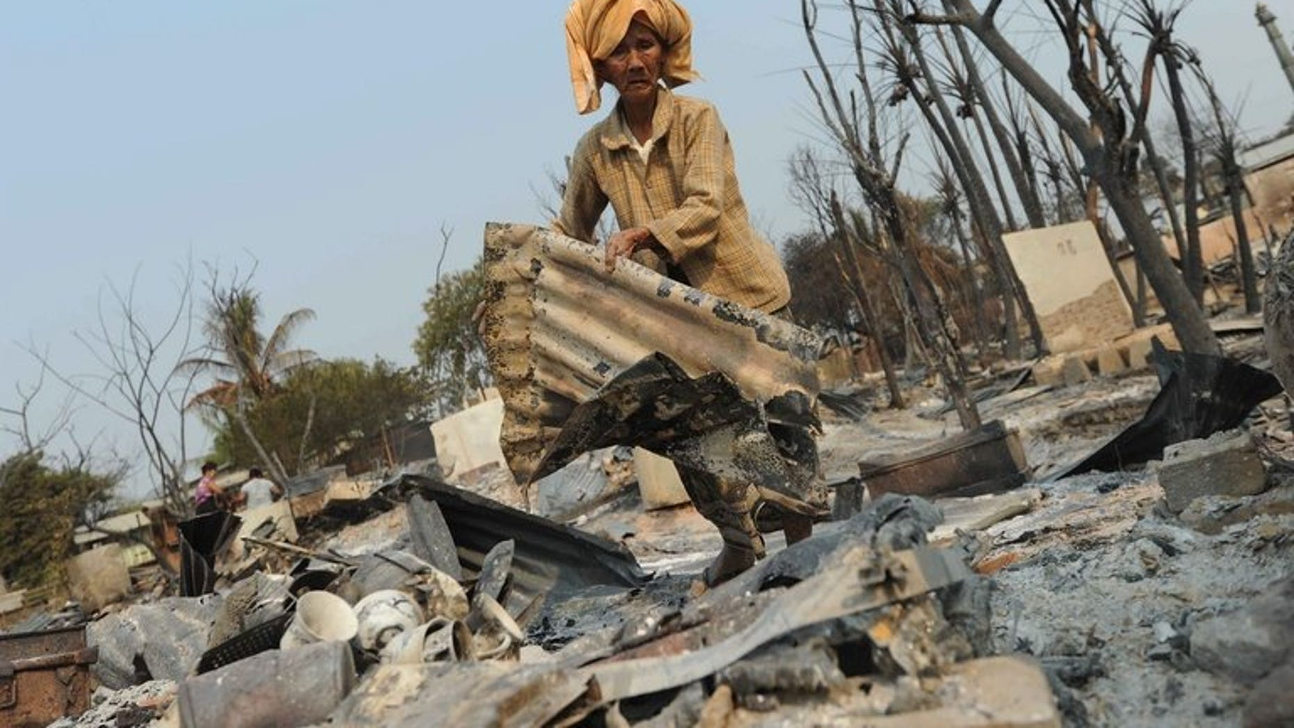 A man searches the remains of a burnt-out house in Meiktila on March 23, 2013. Myanmar has sentenced two Buddhist men to seven years in prison for murders during the religious violence.