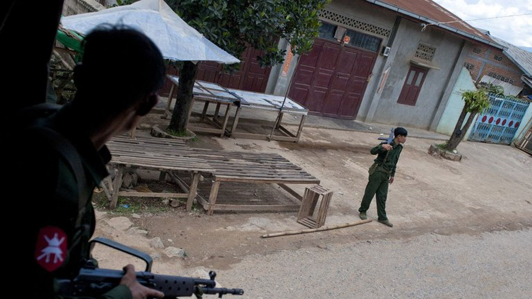 Soldiers stand guard after riots broke out in Lashio, eastern Myanmar, on May 30, 2013. Myanmar has discharged 42 children and young people from its armed forces, UN agencies has said, urging increased efforts to free child soldiers as the country emerges from military rule.