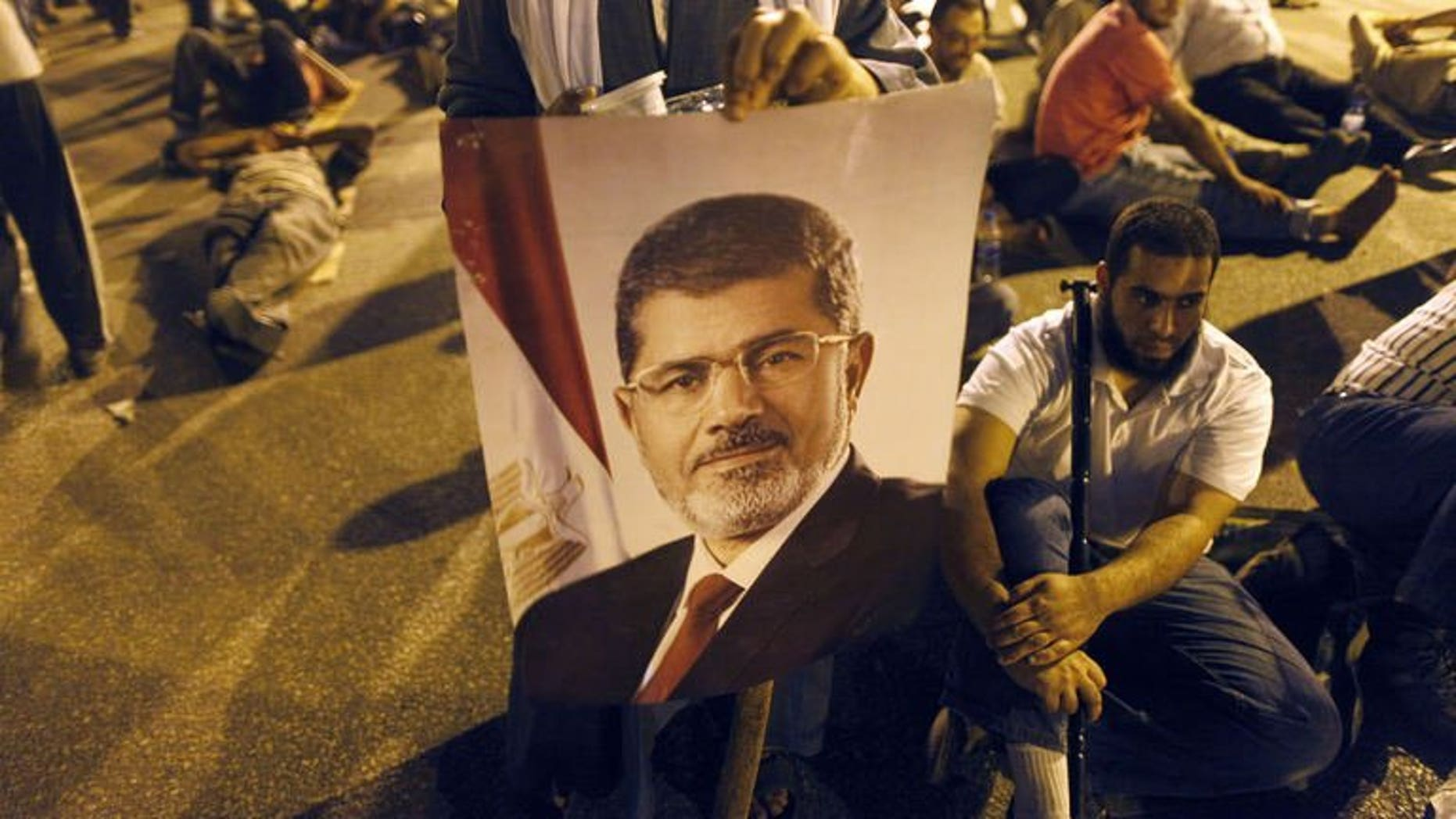 A supporter of the Muslim Brotherhood holds the portraits of deposed president Mohamed Morsi during a rally outside Cairo's Rabaa al-Adawiya mosque late on July 7, 2013. Egypt's prosecution ordered the closure of the Cairo headquarters of the Muslim Brotherhood's Freedom and Justice Party after police found weapons inside it on Monday, a security official said.